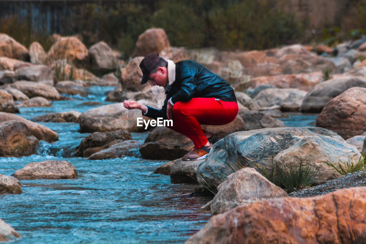 Side view of teenage boy crouching on rock in river