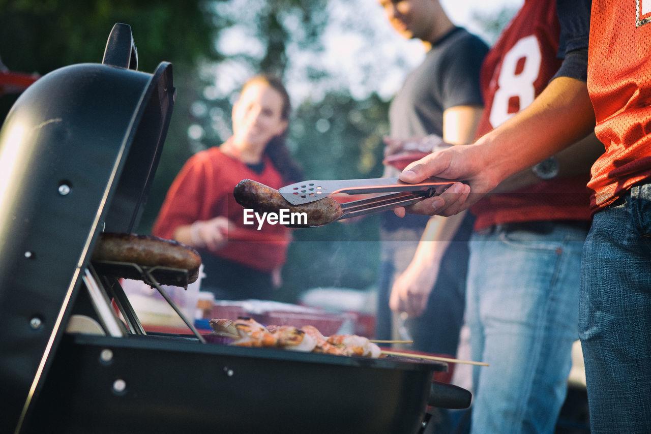 People Preparing Food On Barbecue Grill