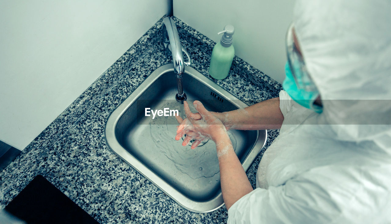 High angle view of doctor washing hands in bathroom sink