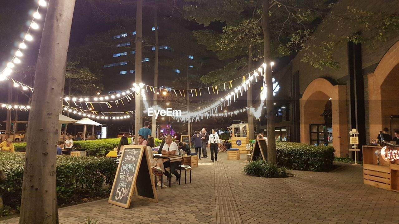 illuminated, lighting equipment, plant, night, group of people, architecture, tree, built structure, decoration, restaurant, incidental people, real people, adult, crowd, business, building exterior, men, women, direction, city, light