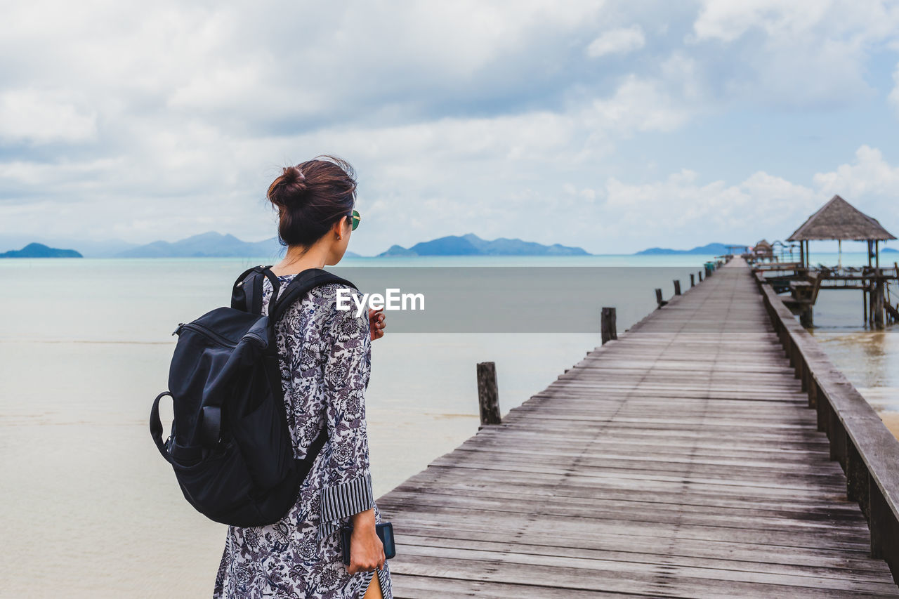 Rear view of woman standing on pier over sea against sky