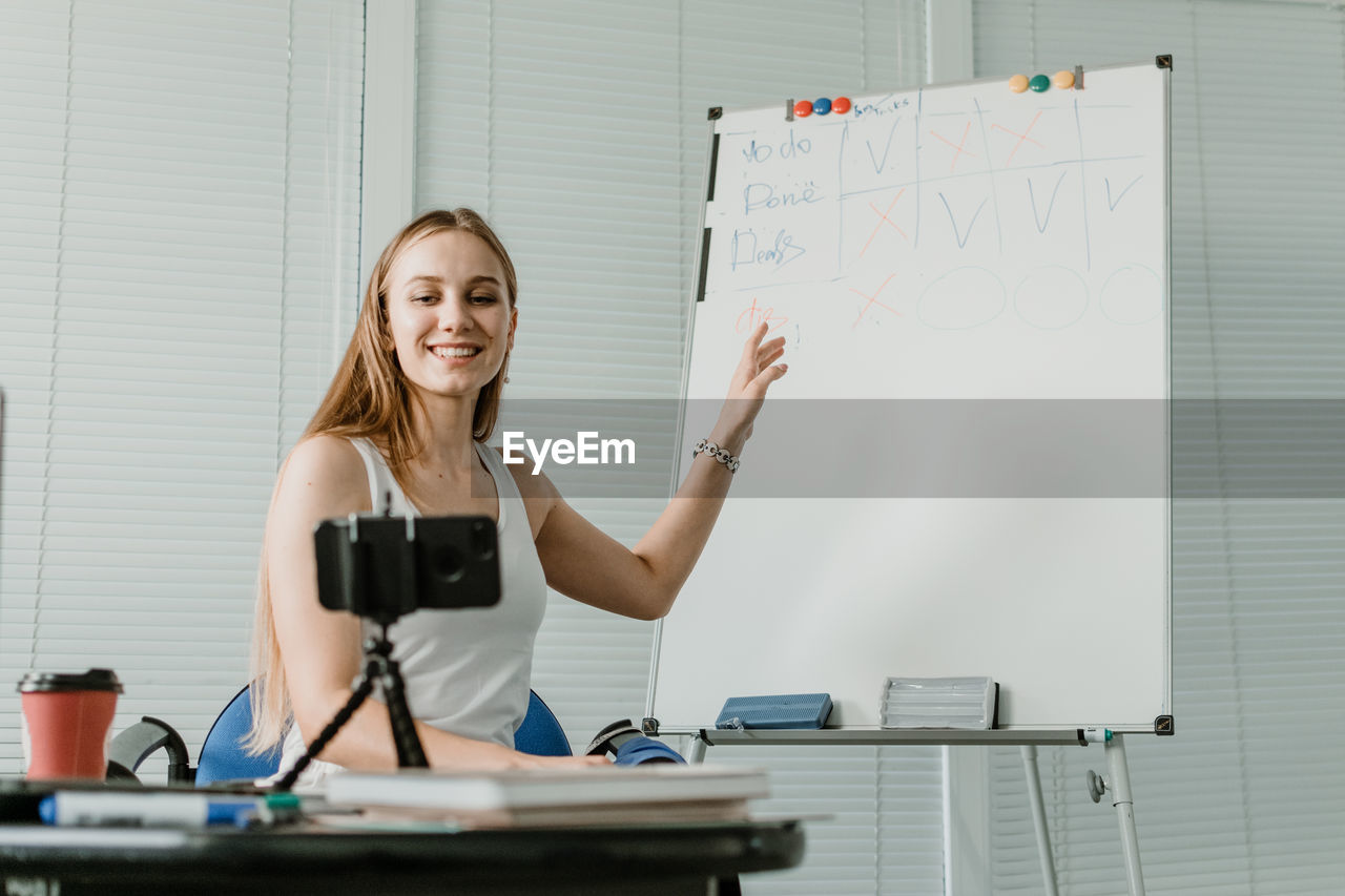 Smiling young woman explaining over whiteboard while blogging with smart phone at home