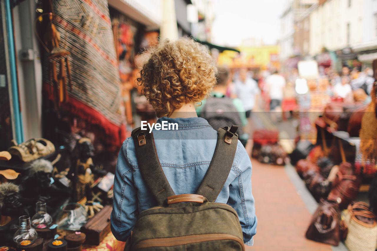 Rear View Of Woman Walking Through Street Market Stalls In City