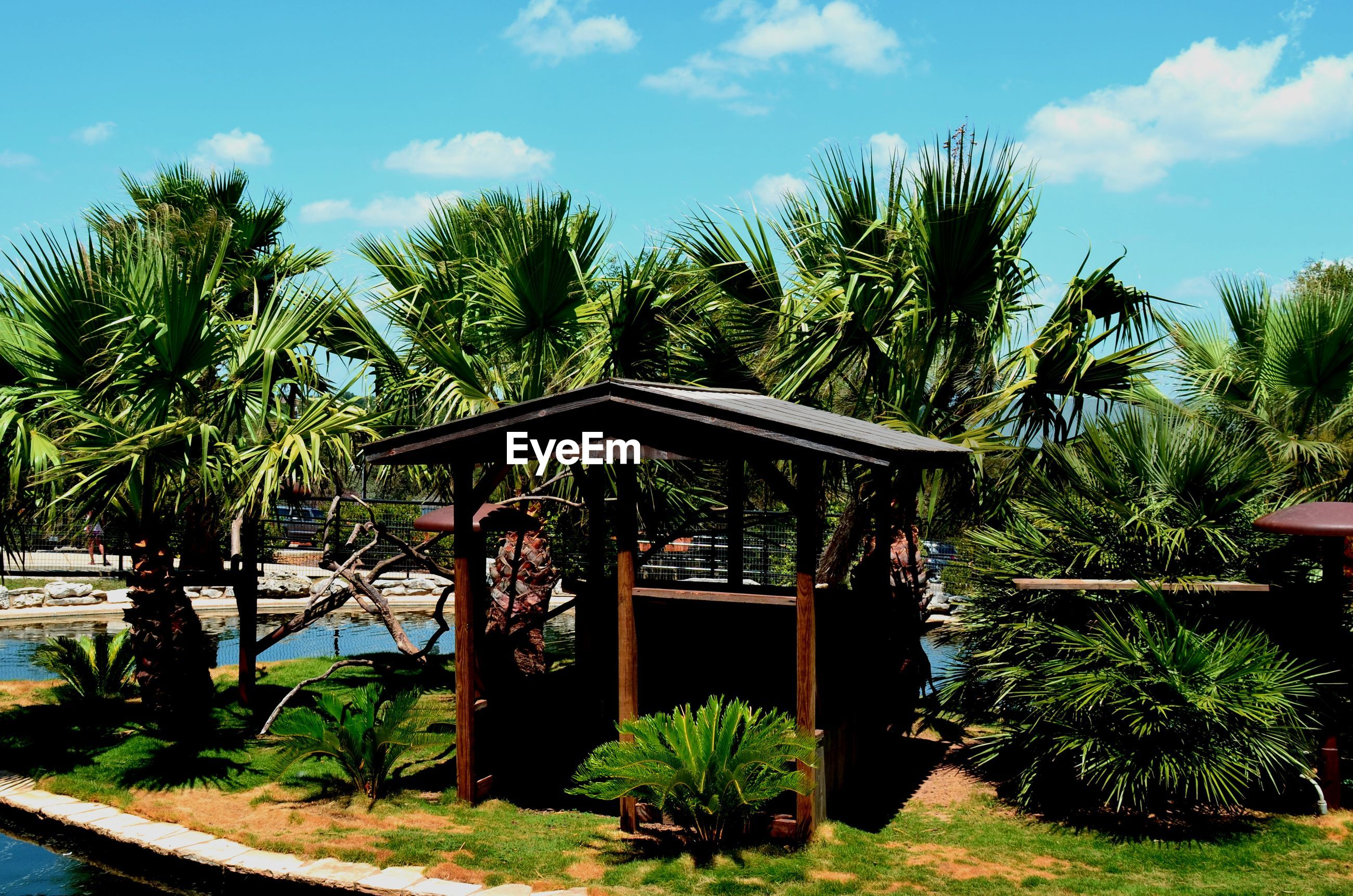 GAZEBO BY PALM TREES AGAINST SKY