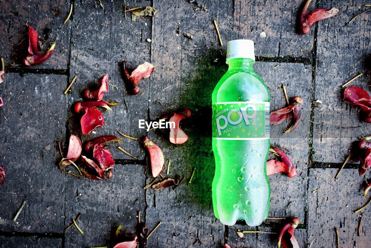 bottle, wood - material, high angle view, food and drink, no people, text, green color, container, red, directly above, drink, food, still life, western script, day, outdoors, communication, refreshment, close-up