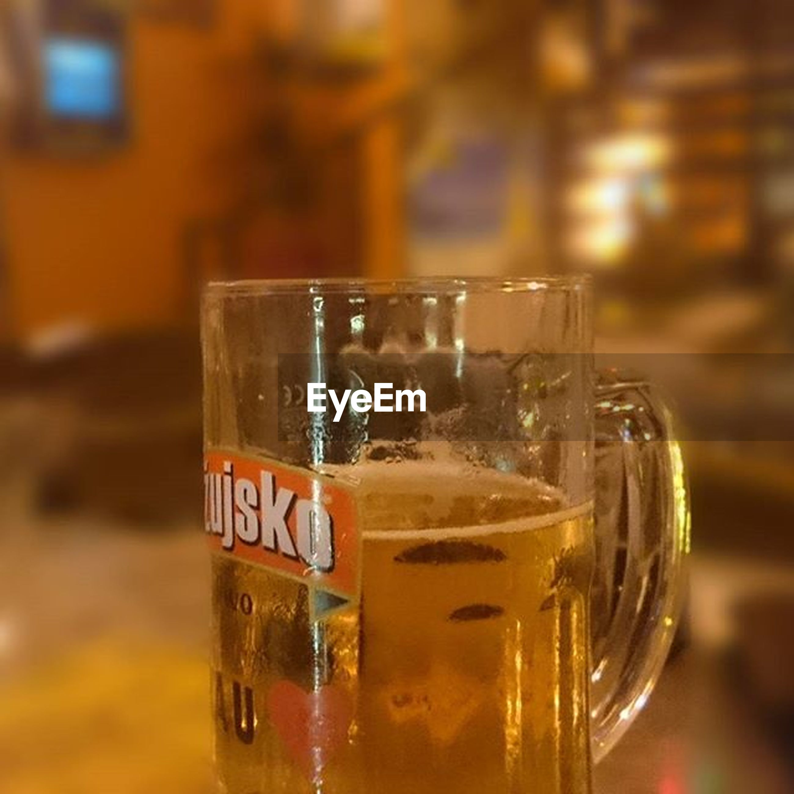 drink, food and drink, refreshment, focus on foreground, close-up, glass - material, alcohol, drinking glass, freshness, indoors, transparent, beer - alcohol, text, beer glass, selective focus, still life, table, western script, frothy drink, communication