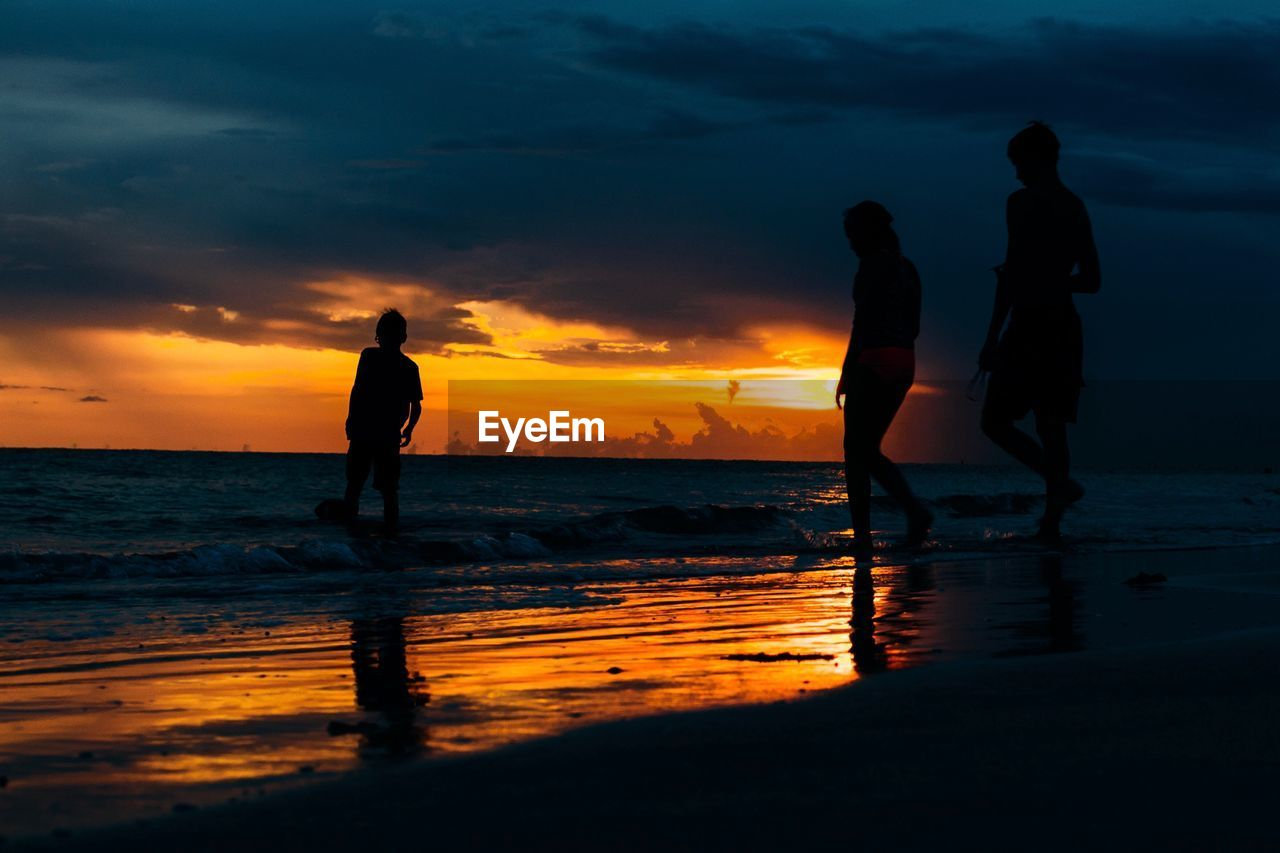 sunset, sky, water, sea, silhouette, cloud - sky, beach, orange color, land, beauty in nature, real people, scenics - nature, standing, horizon over water, men, lifestyles, leisure activity, nature, horizon, outdoors