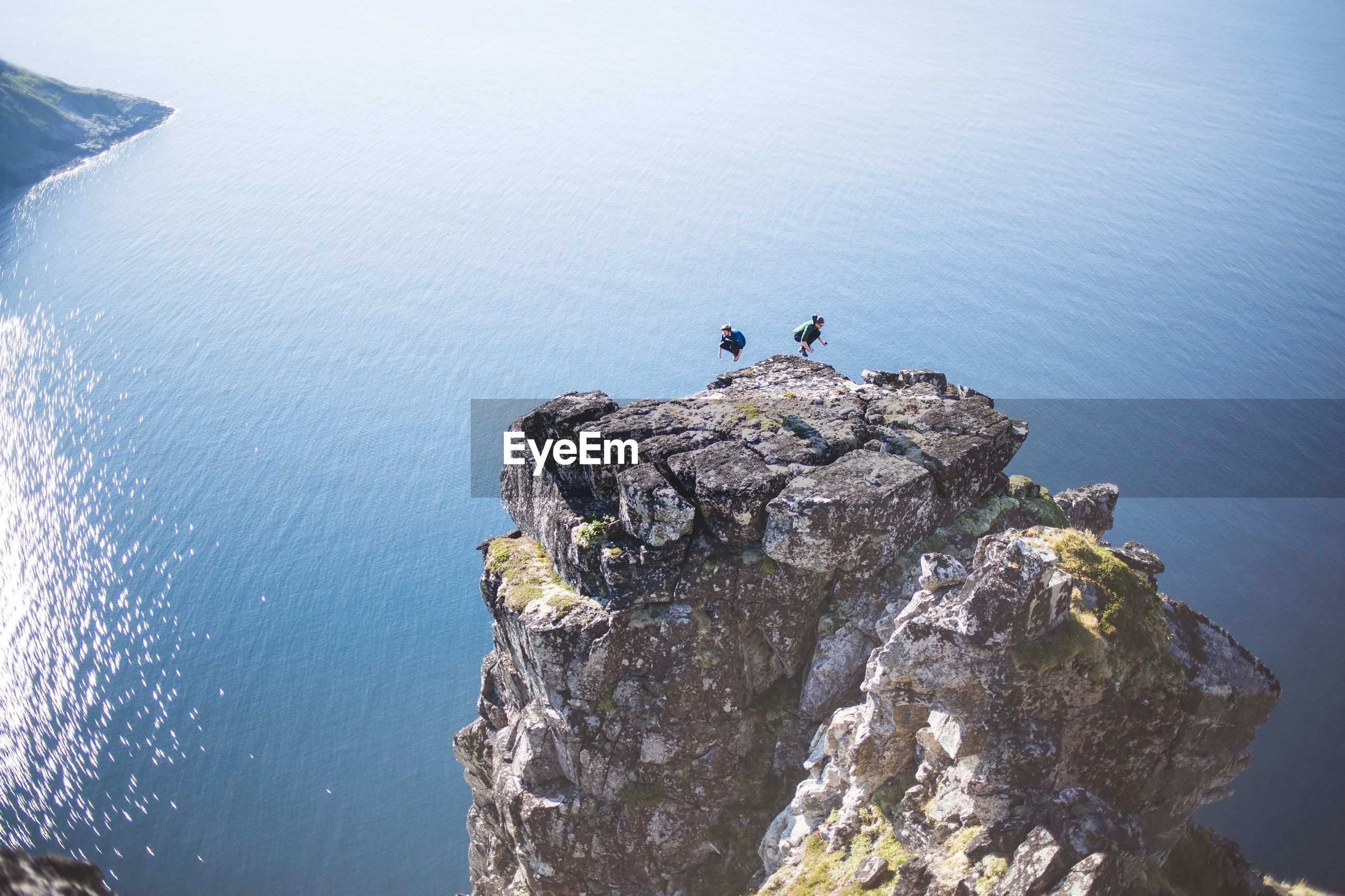 High angle view of man and woman jumping on cliff