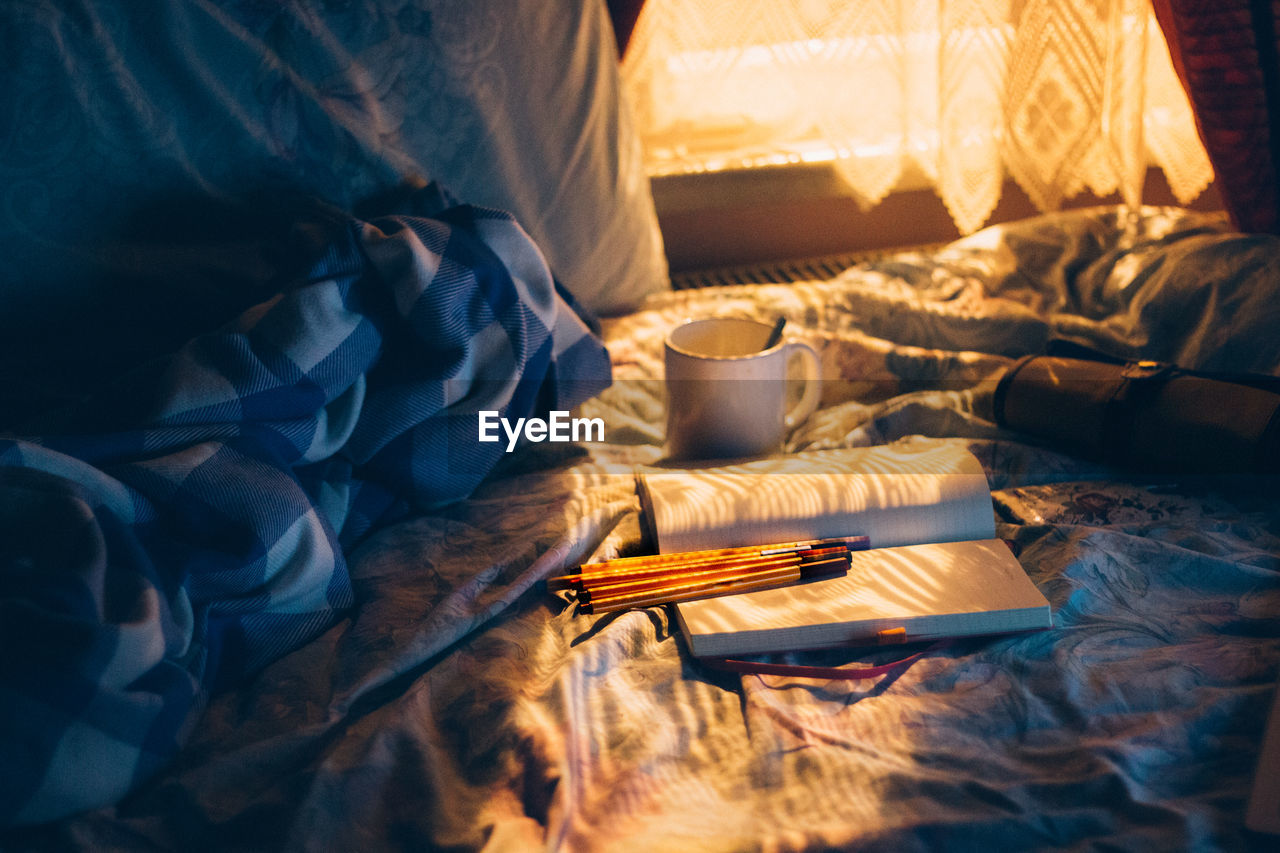 Coffee Cup By Book And Pencils On Bed By At Home