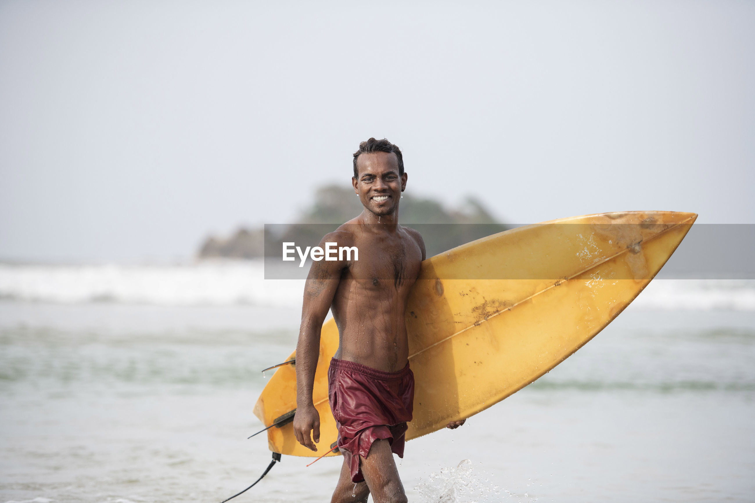 Portrait of shirtless male surfer carrying surfboard in sea