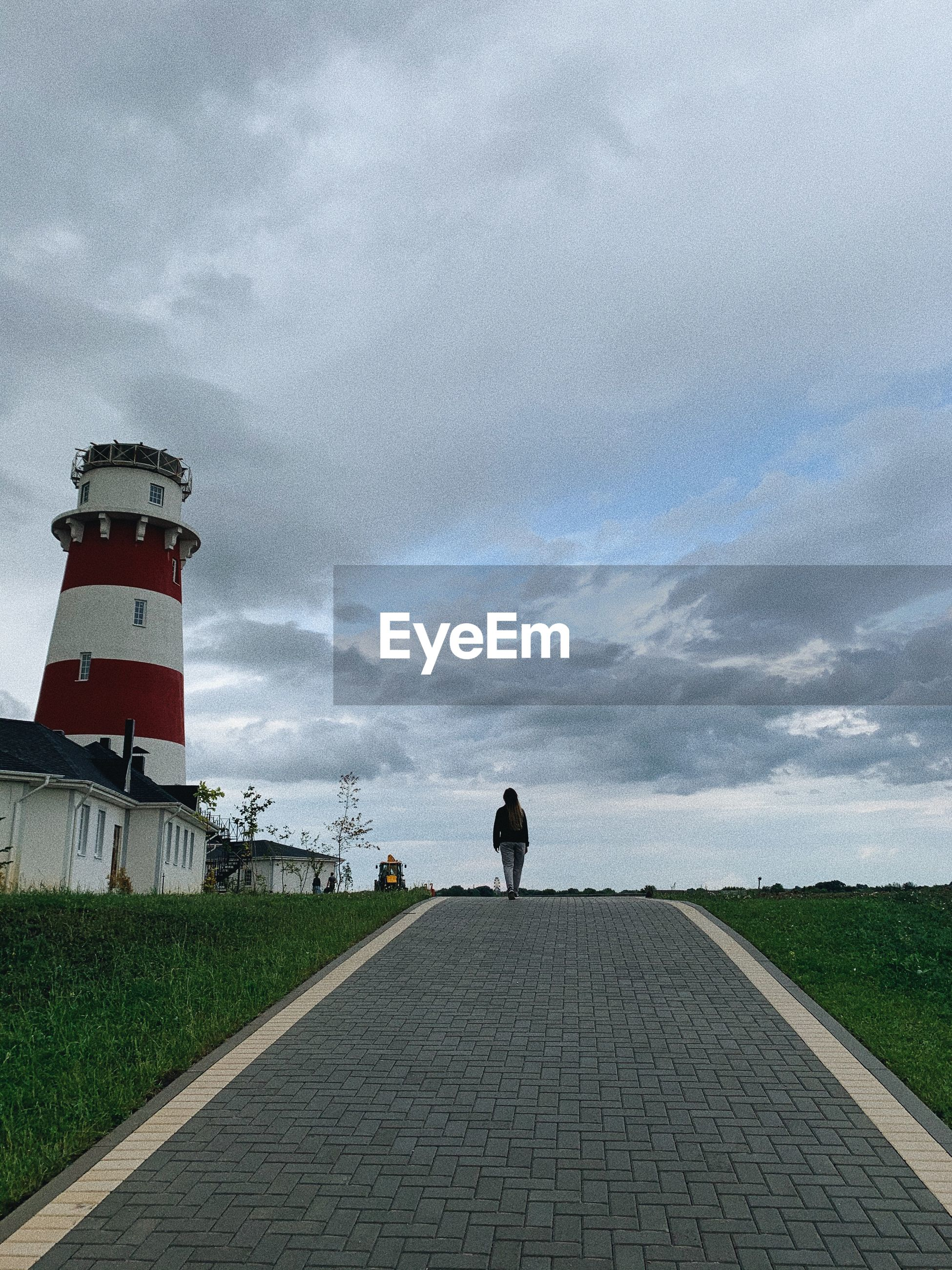 REAR VIEW OF MAN WALKING ON FOOTPATH BY LIGHTHOUSE