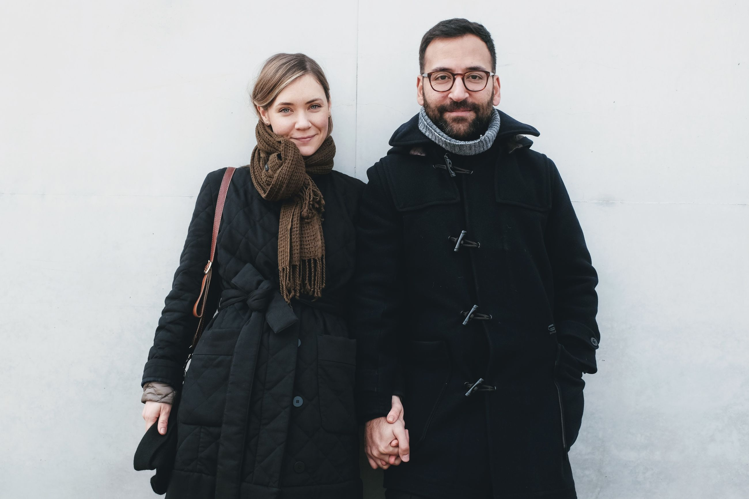 Portrait of couple standing against wall