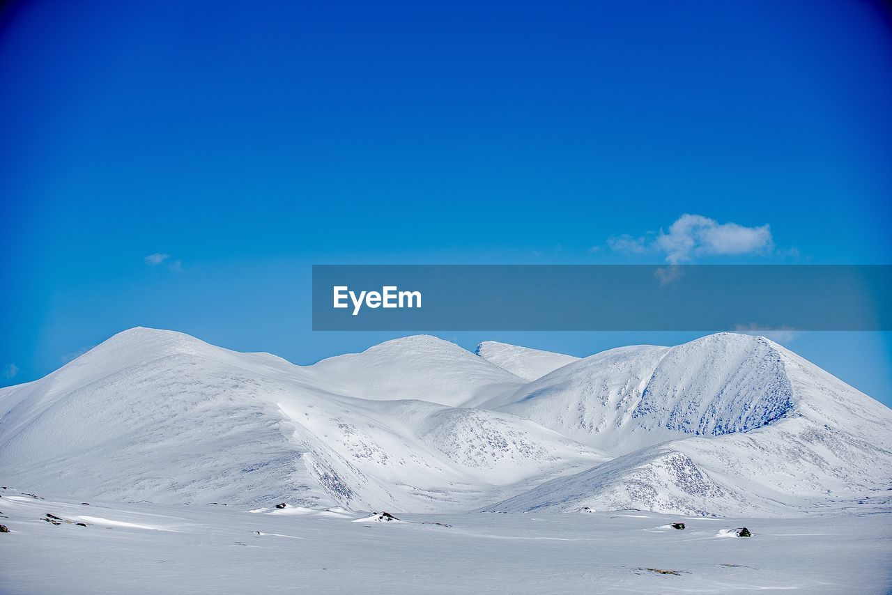 LOW ANGLE VIEW OF SNOW LANDSCAPE AGAINST BLUE SKY