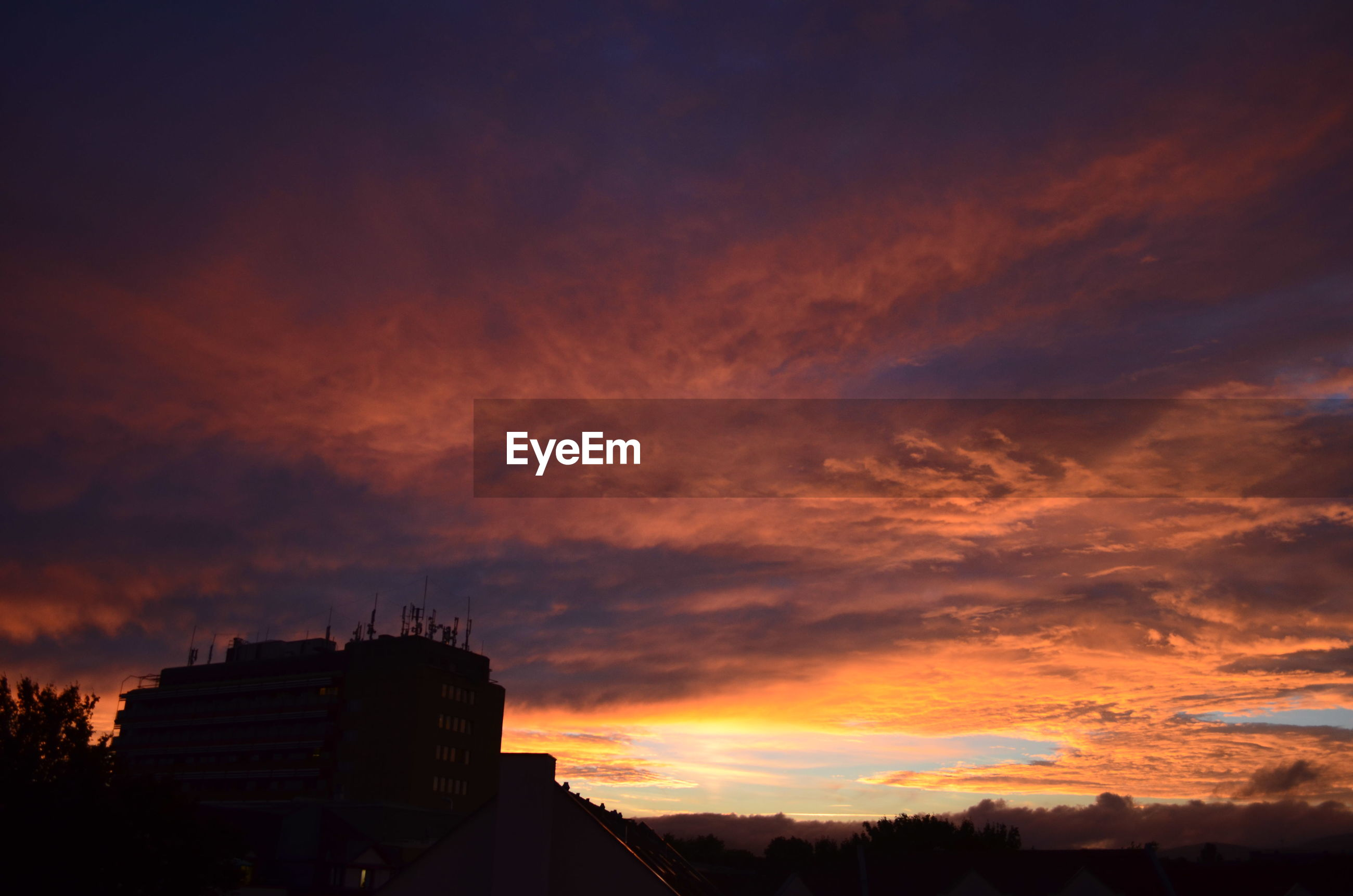 sunset, architecture, built structure, building exterior, silhouette, sky, dusk, city, high section, scenics, cloud - sky, cloud, orange color, outdoors, dramatic sky, nature, tranquility, tall - high, beauty in nature, tranquil scene, no people, moody sky, city life, majestic, storm cloud, cloudscape, atmospheric mood