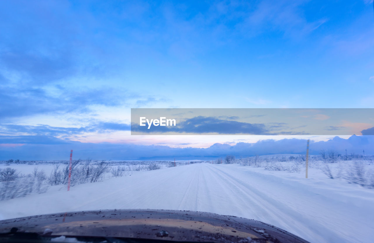 transportation, snow, cold temperature, winter, nature, scenics, weather, road, windshield, sky, beauty in nature, mode of transport, no people, tranquil scene, the way forward, car point of view, car, cloud - sky, blue, landscape, tranquility, land vehicle, outdoors, day, mountain