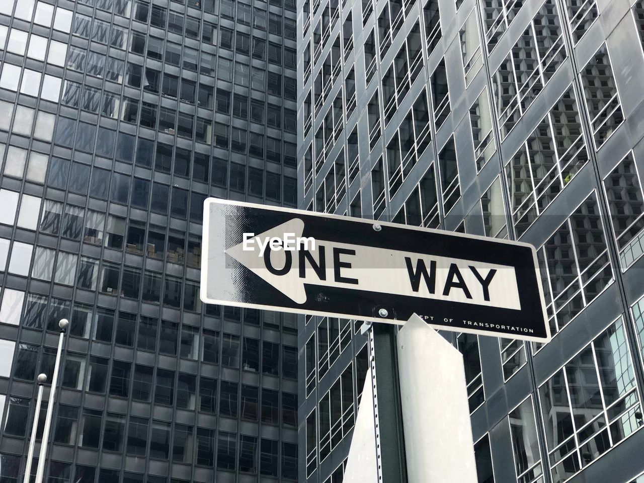 architecture, communication, built structure, building exterior, sign, one way, guidance, text, road sign, arrow symbol, directional sign, city, building, office, direction, office building exterior, western script, no people, low angle view, symbol, outdoors, skyscraper