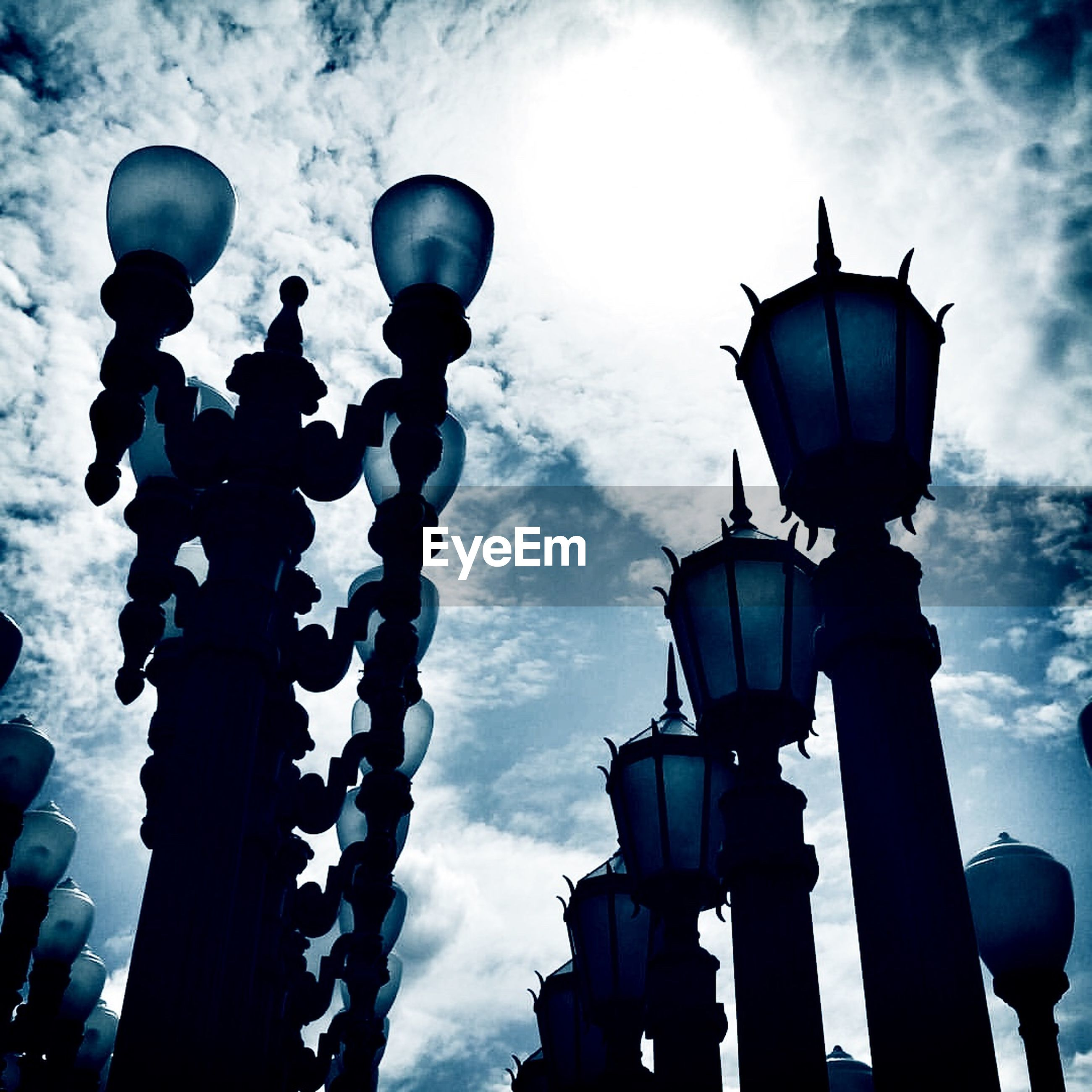 Low angle view of lamp posts against cloudy sky