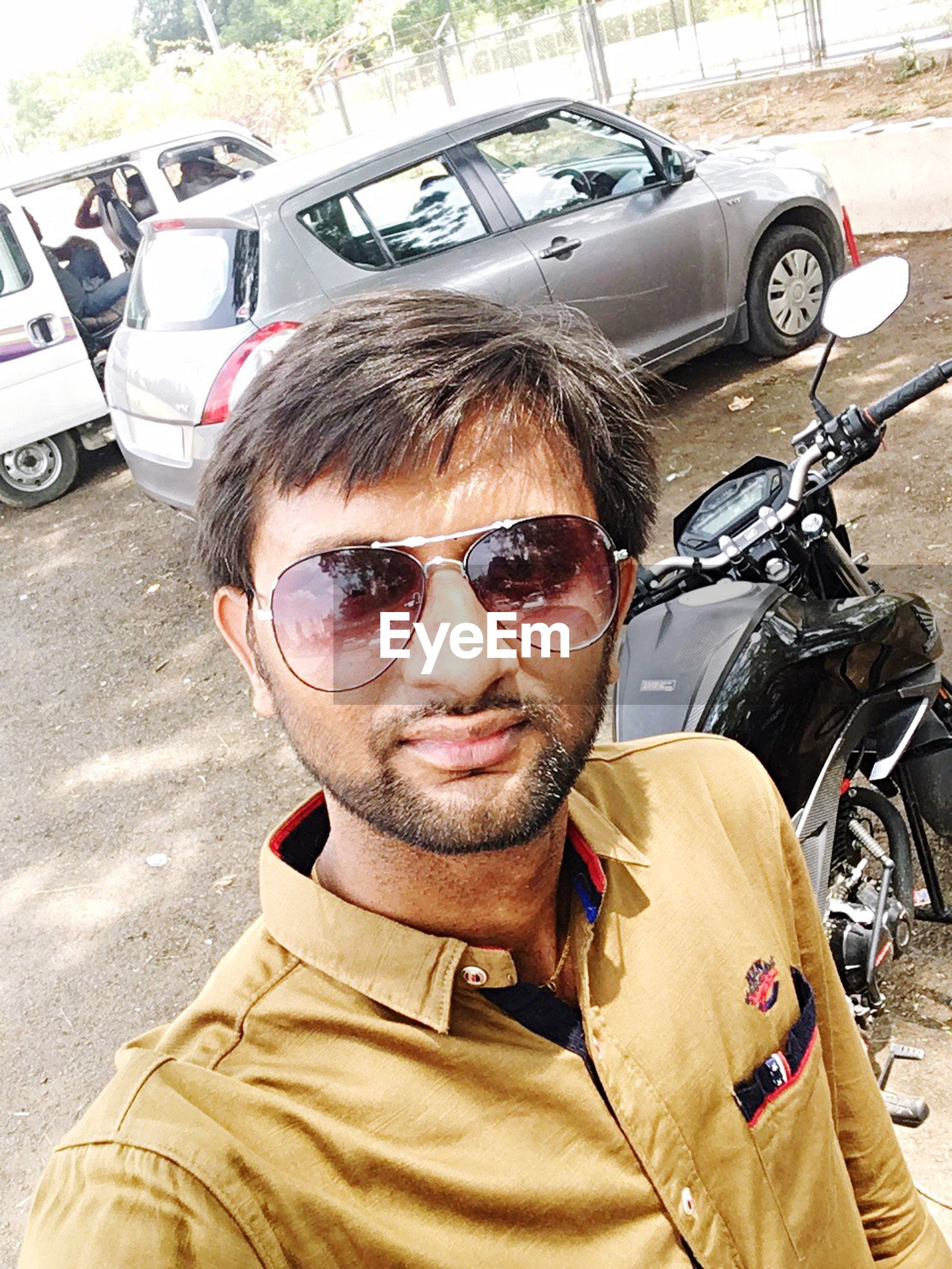 sunglasses, transportation, car, mode of transport, land vehicle, one person, mid adult men, day, young adult, young men, real people, front view, outdoors, portrait, headshot, casual clothing, looking at camera, one man only, adults only, adult, people