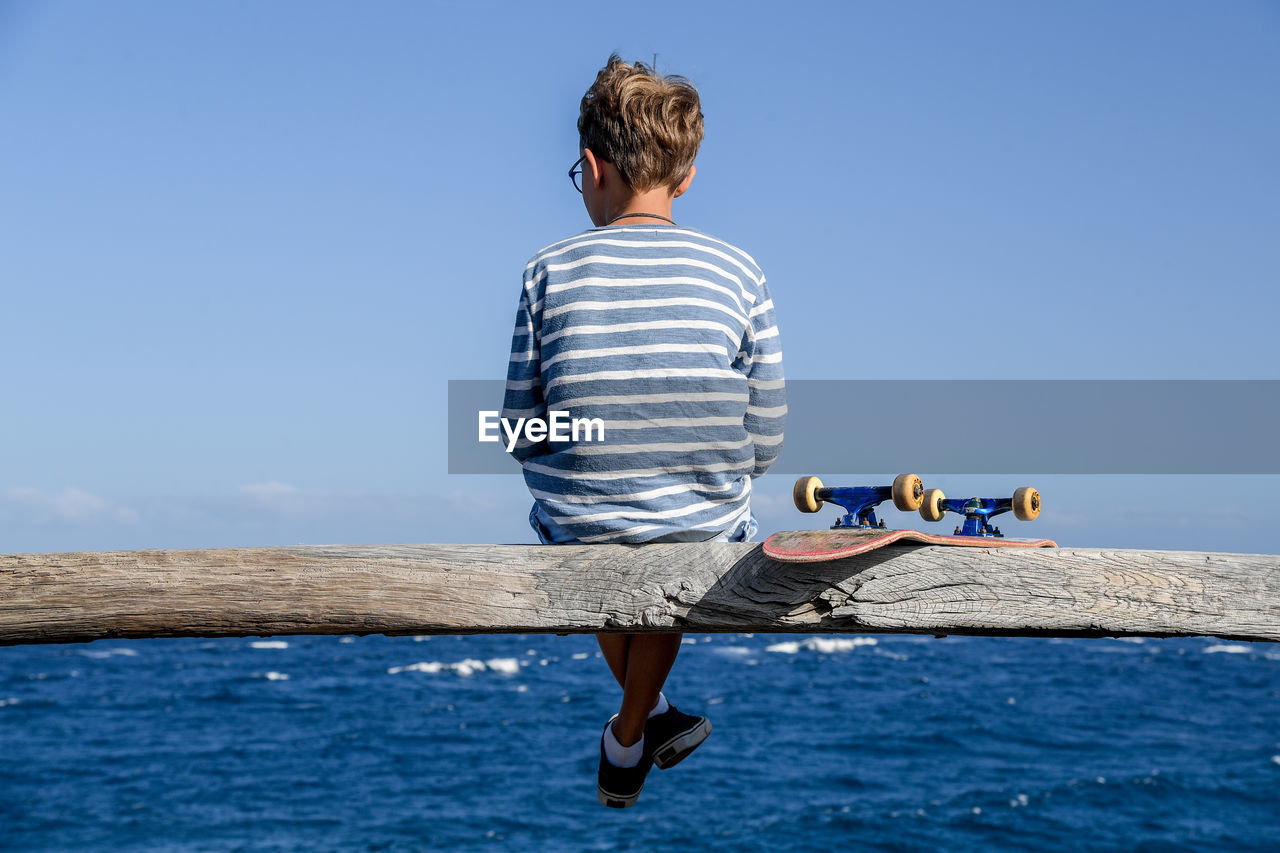 one person, water, striped, leisure activity, real people, casual clothing, rear view, sky, lifestyles, sea, nature, men, day, full length, boys, clear sky, blue, sunlight, outdoors, shorts