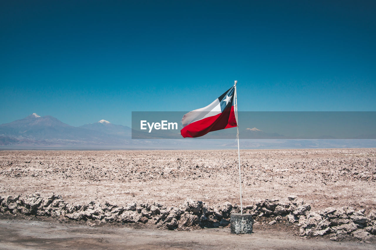 flag, environment, sky, patriotism, mountain, scenics - nature, nature, day, beauty in nature, tranquil scene, no people, non-urban scene, land, landscape, blue, copy space, tranquility, wind, outdoors, climate, arid climate, salt flat