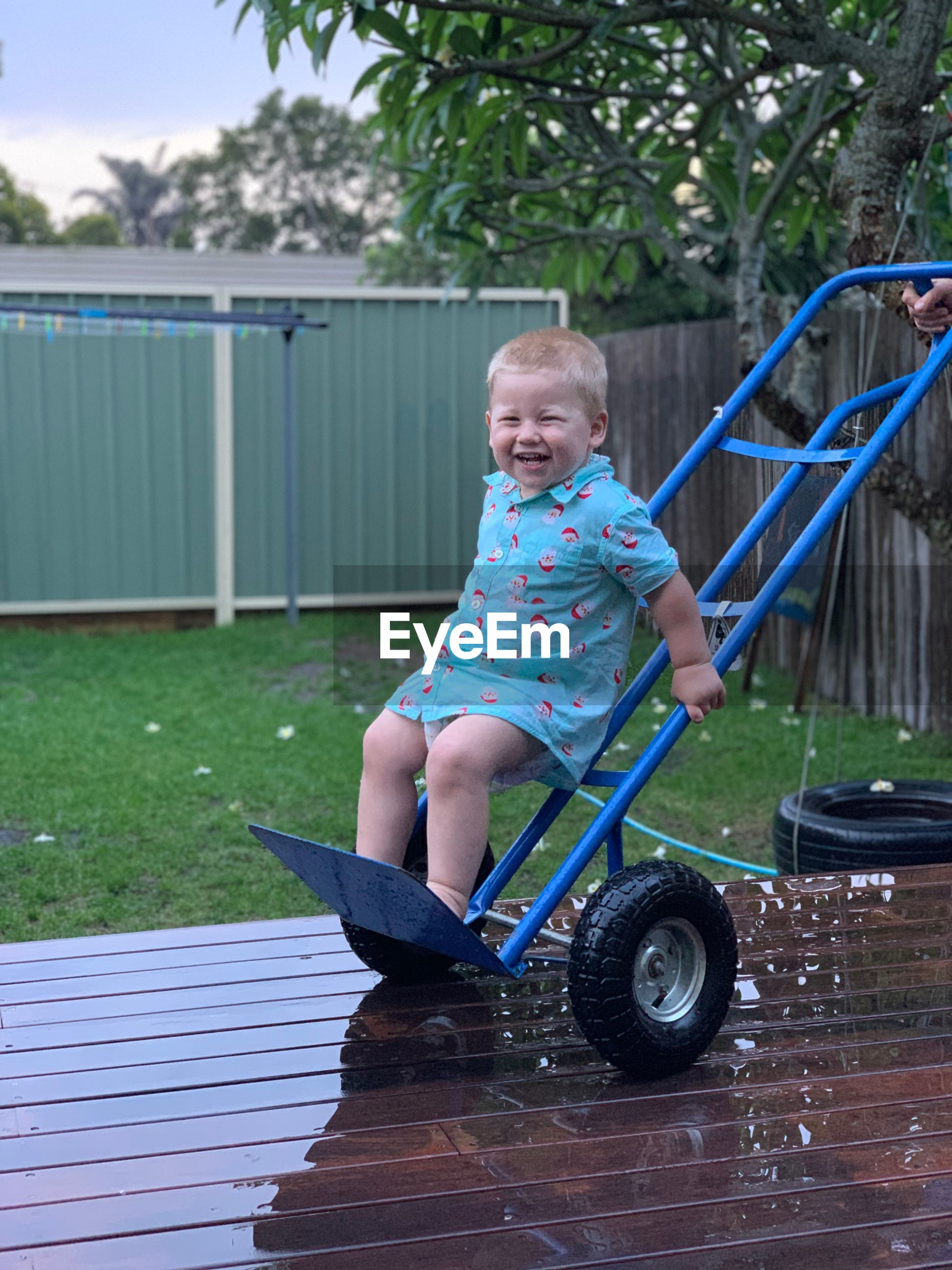 Baby boy standing on hand truck and smiling