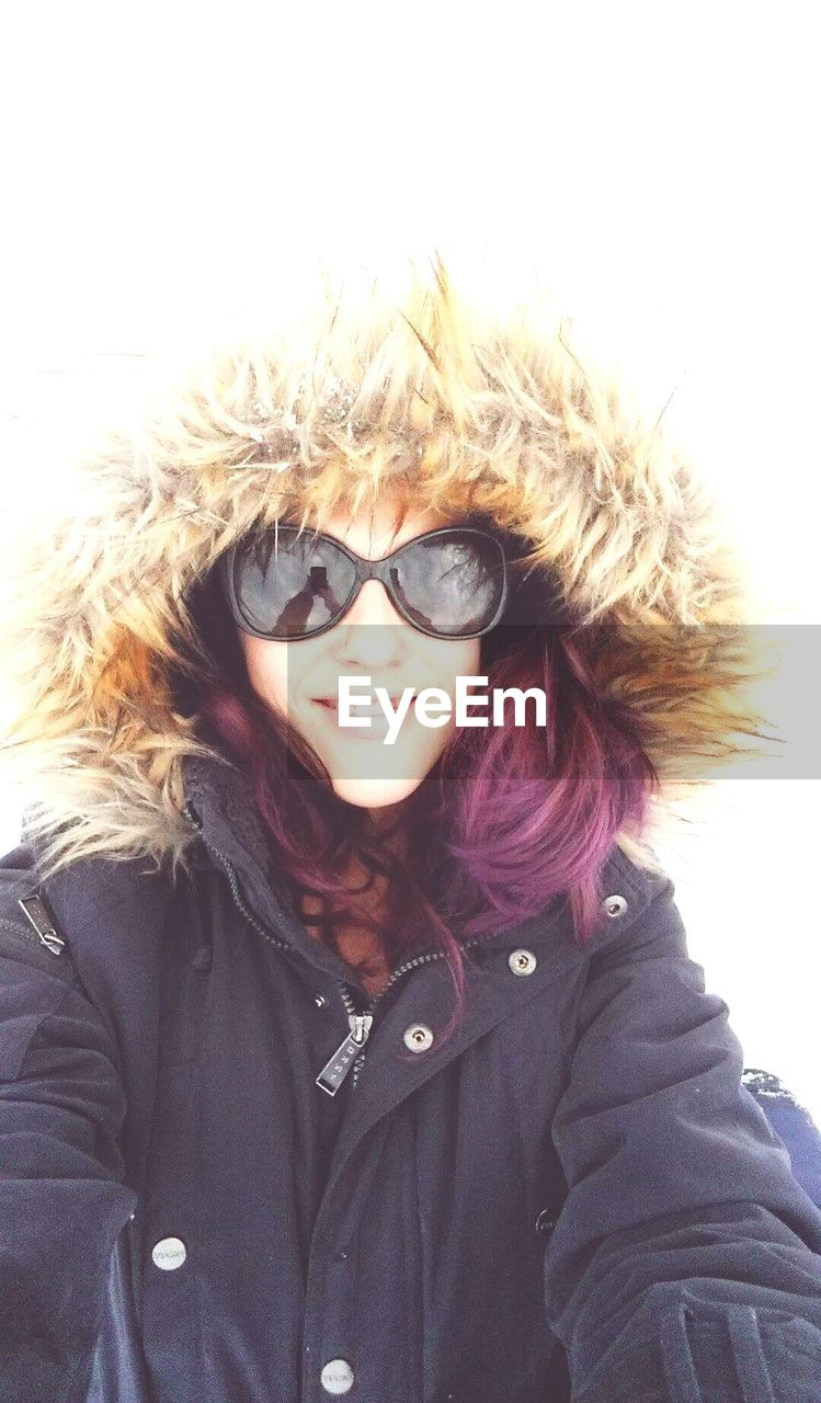 looking at camera, winter, real people, front view, warm clothing, cold temperature, snow, portrait, one person, sunglasses, lifestyles, smiling, leisure activity, jacket, happiness, outdoors, nature, day, young women, headshot, young adult, clear sky, close-up, white background, sky