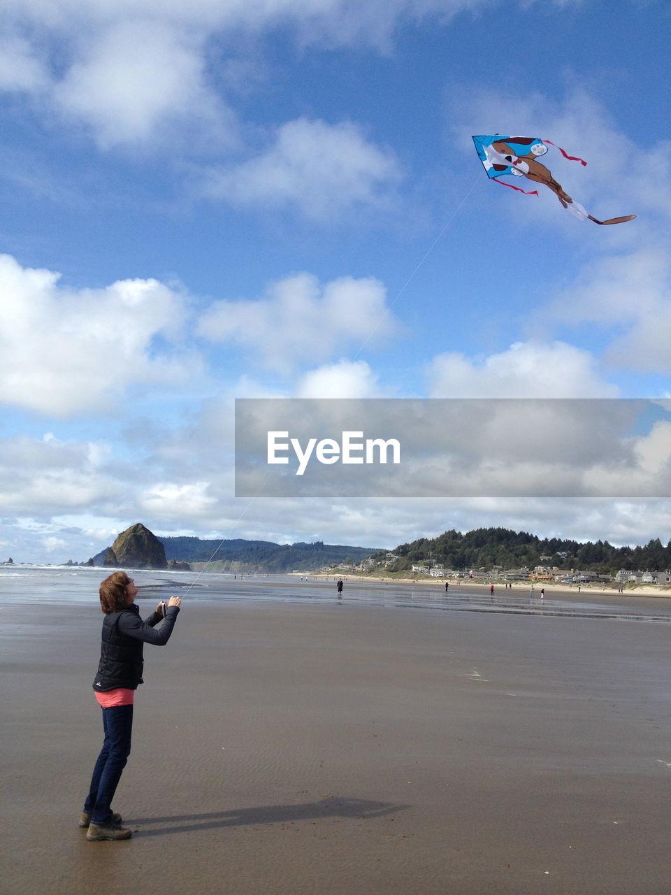 Full length of boy flying over beach against sky