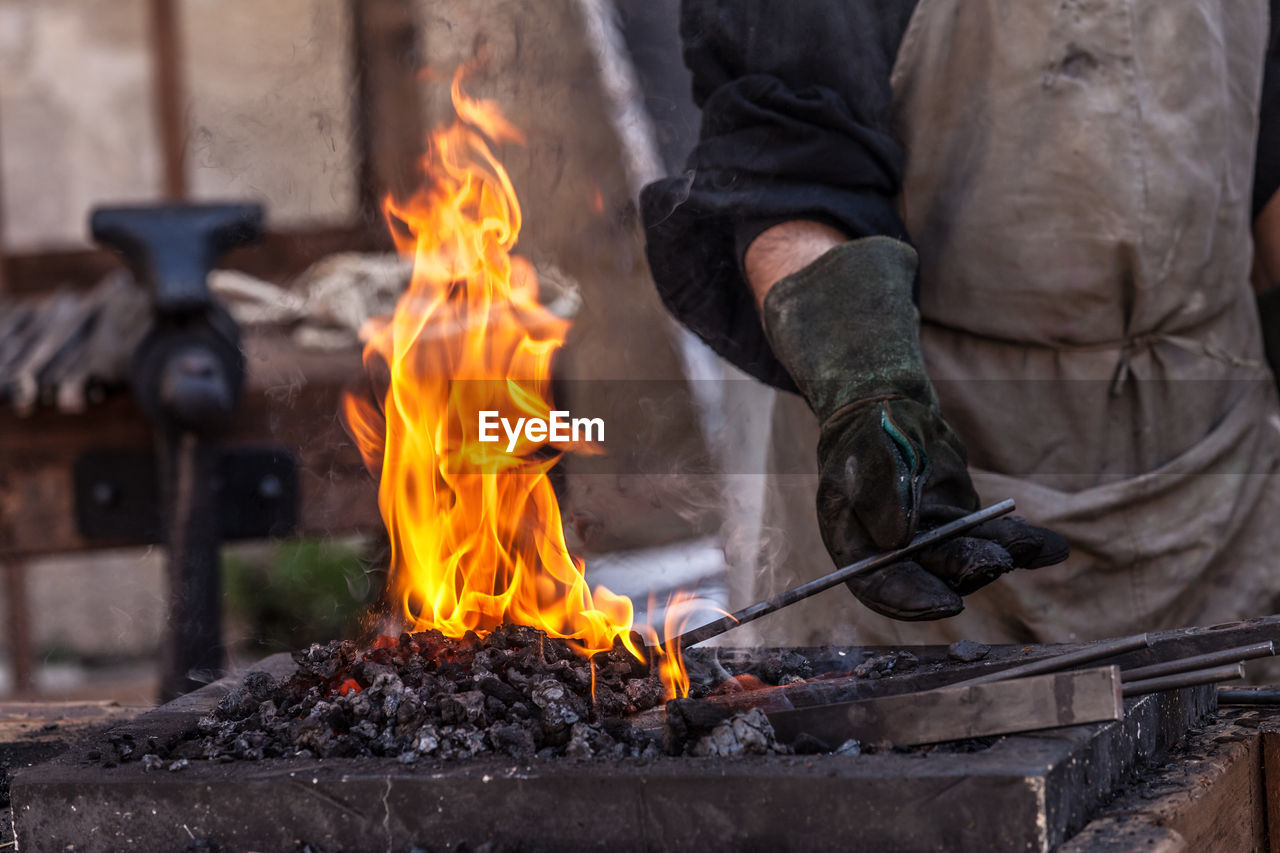 Midsection Of Man Holding Metal In Bonfire At Workshop