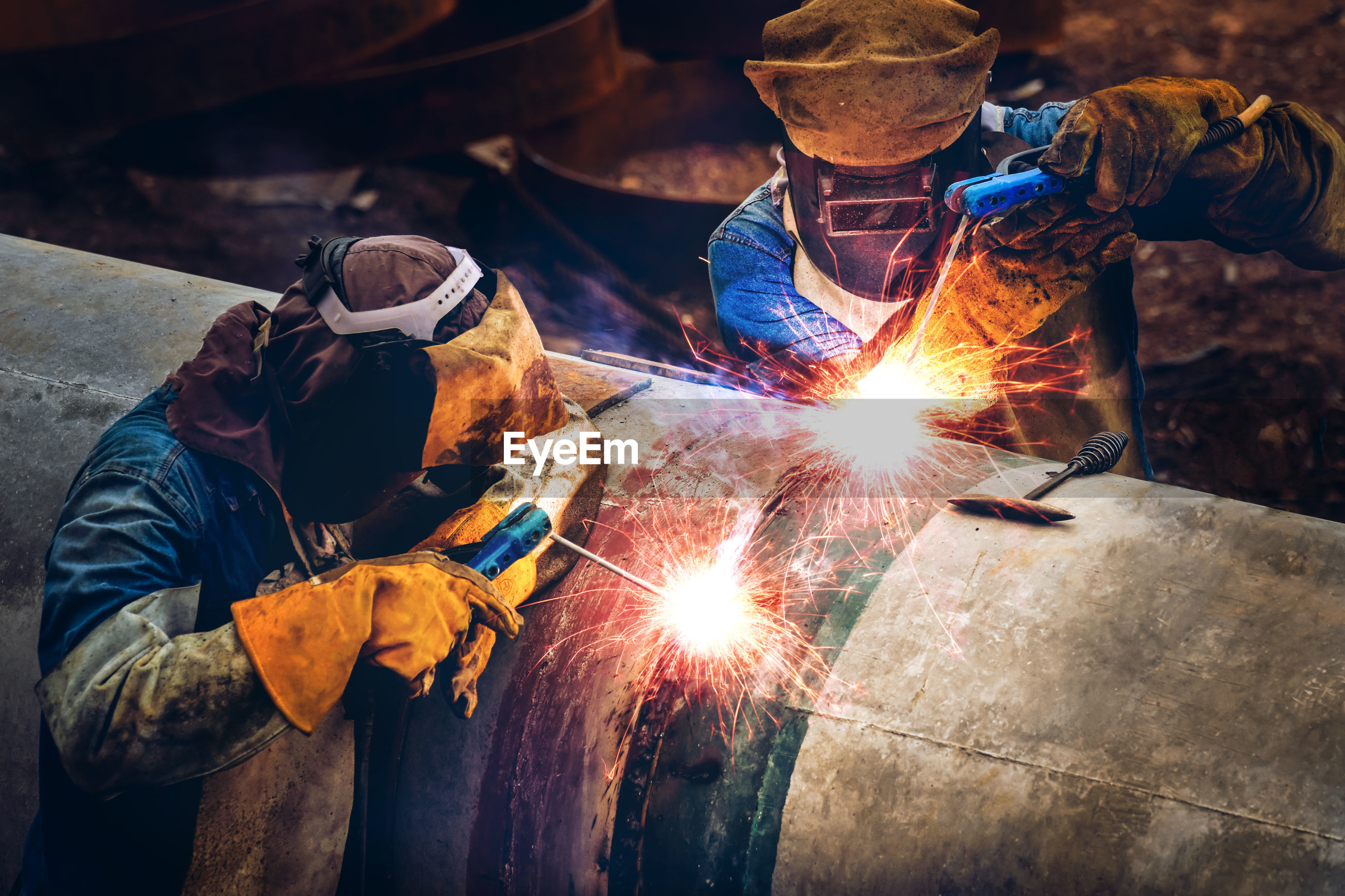 Men working on metal structure in factory