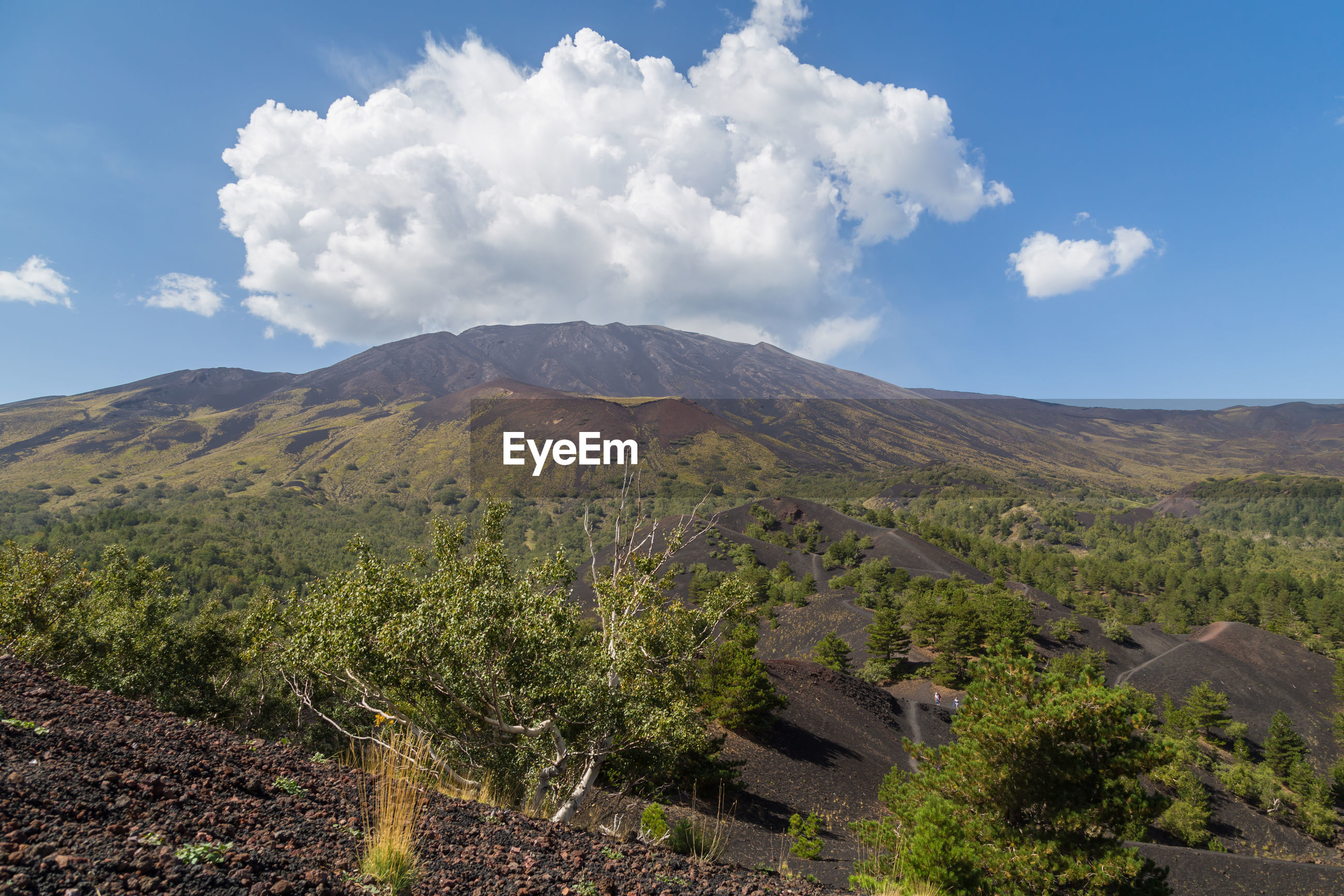 Scenic view of landscape around mount etna with rising steam clouds against blue sky