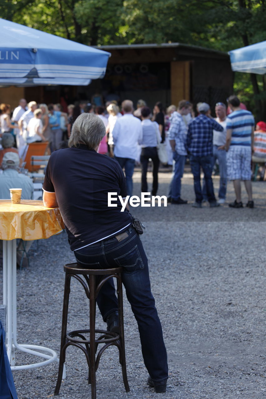 real people, men, group of people, crowd, people, adult, seat, rear view, lifestyles, full length, leisure activity, women, focus on foreground, city, casual clothing, sitting, architecture, chair, table