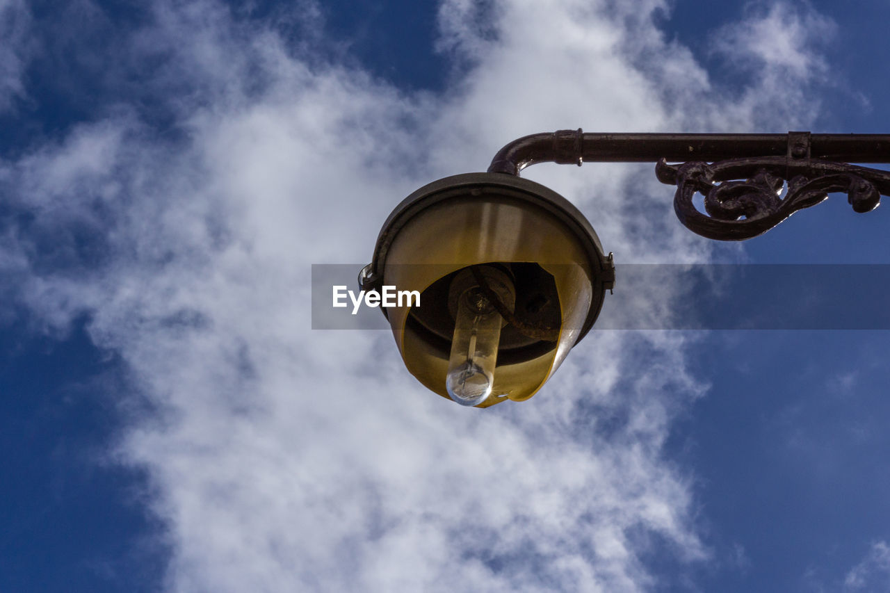 cloud - sky, low angle view, sky, nature, day, no people, outdoors, lighting equipment, street light, street, metal, mid-air, built structure, industry, light, architecture, blue, hanging, construction industry, electric lamp