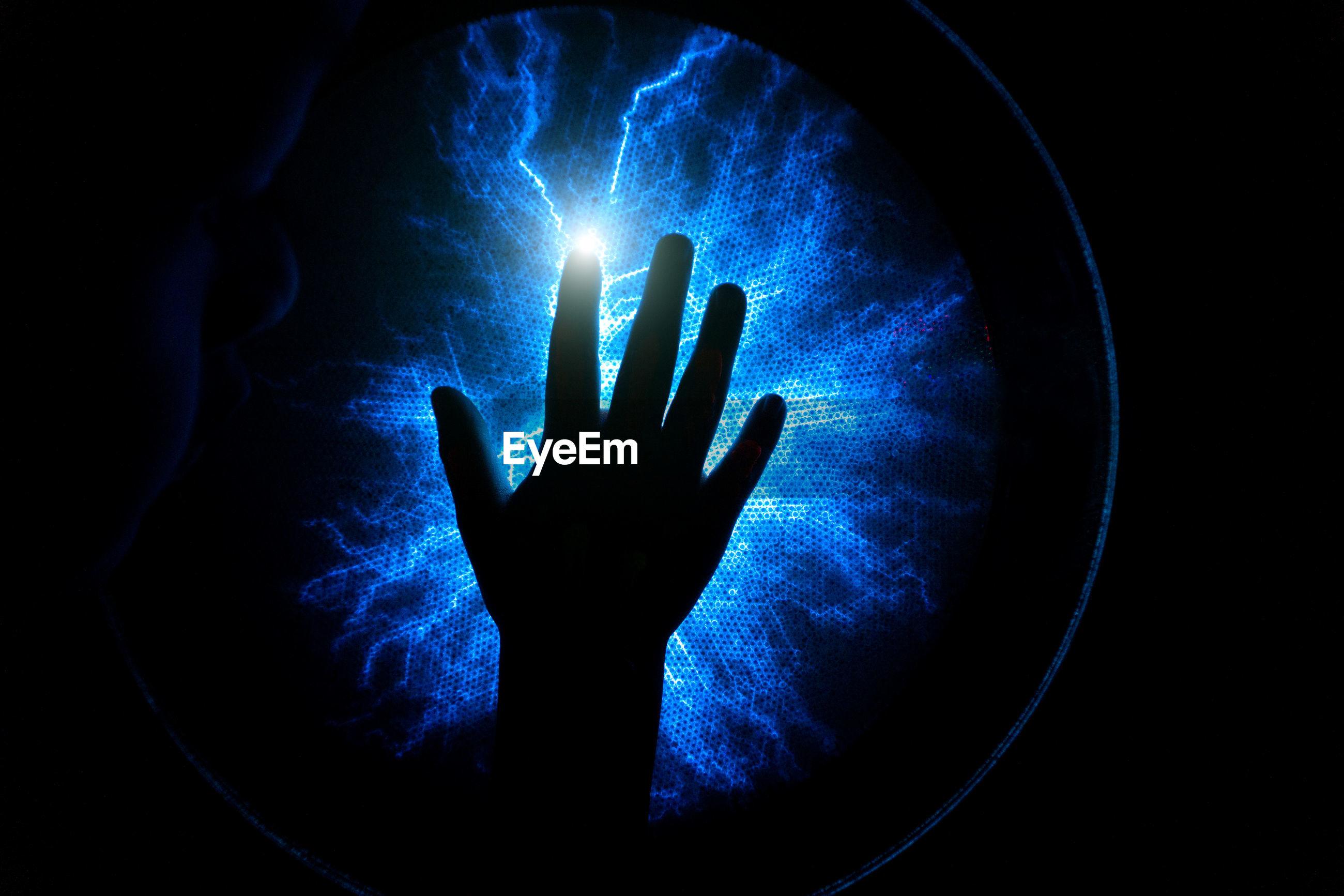 Cropped hand against illuminated lighting equipment in darkroom