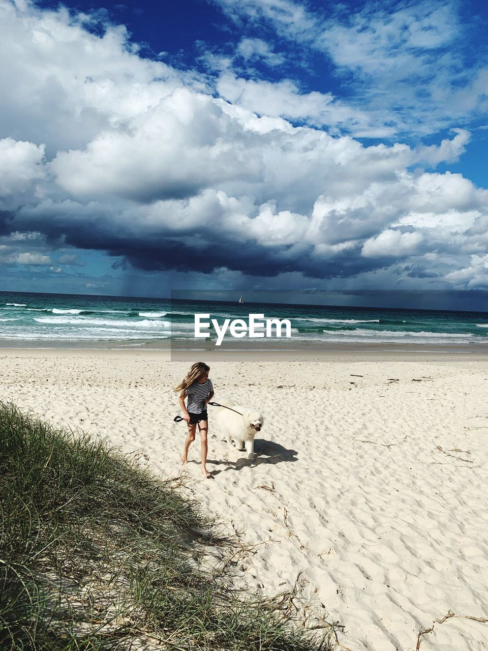 beach, land, sea, sky, water, cloud - sky, sand, horizon over water, one person, horizon, beauty in nature, scenics - nature, real people, full length, nature, one animal, pets, day, domestic, outdoors