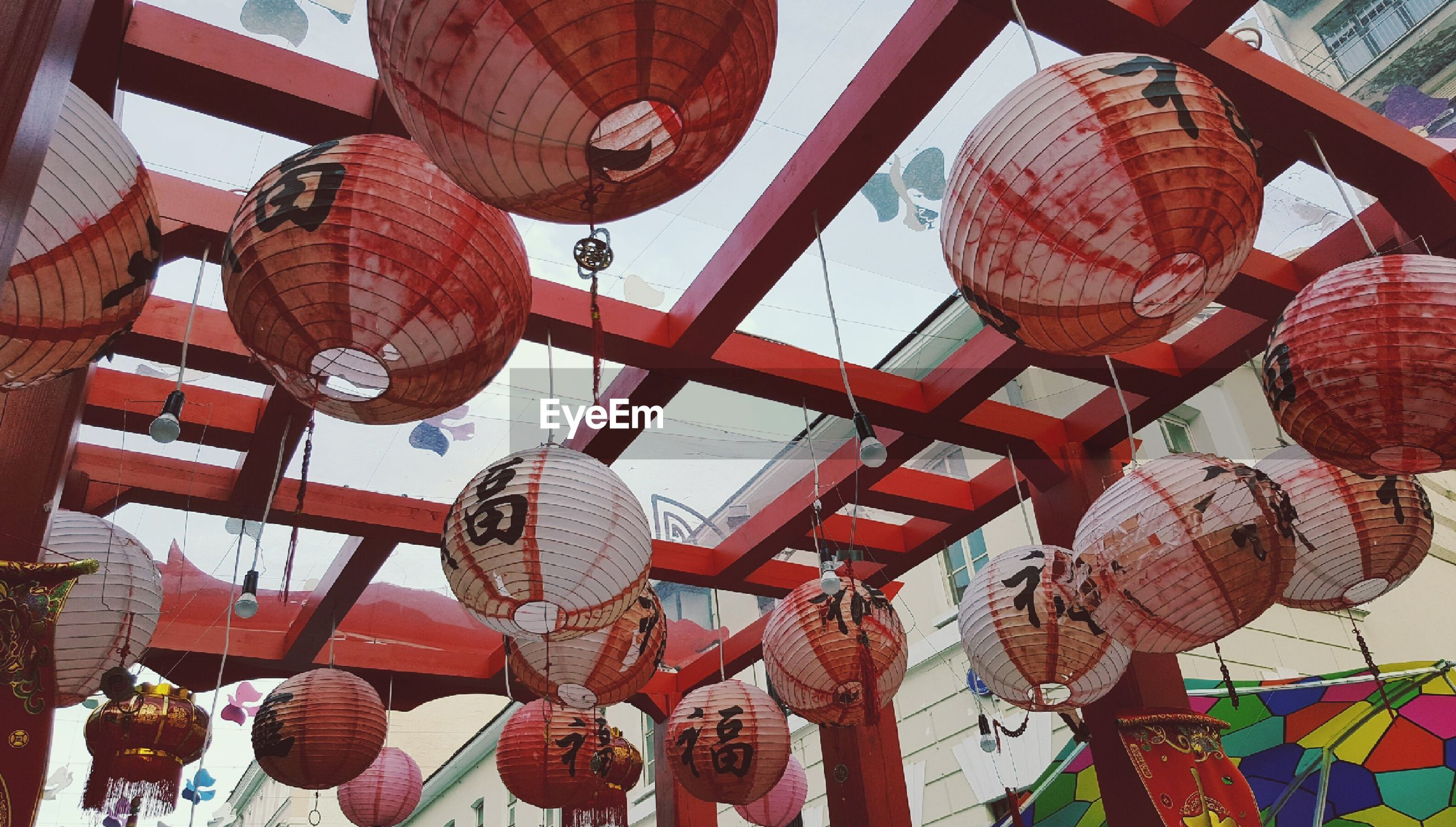 Low angle view of chinese paper lanterns hanging from red wooden structure at chinatown
