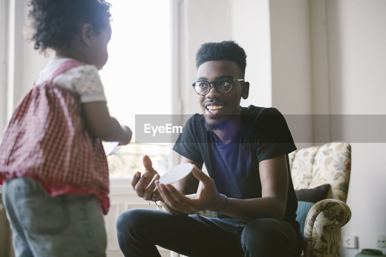 child, two people, sitting, three quarter length, togetherness, casual clothing, real people, childhood, women, glasses, emotion, lifestyles, family, indoors, females, smiling, leisure activity, eyeglasses, girls, men, positive emotion, hairstyle