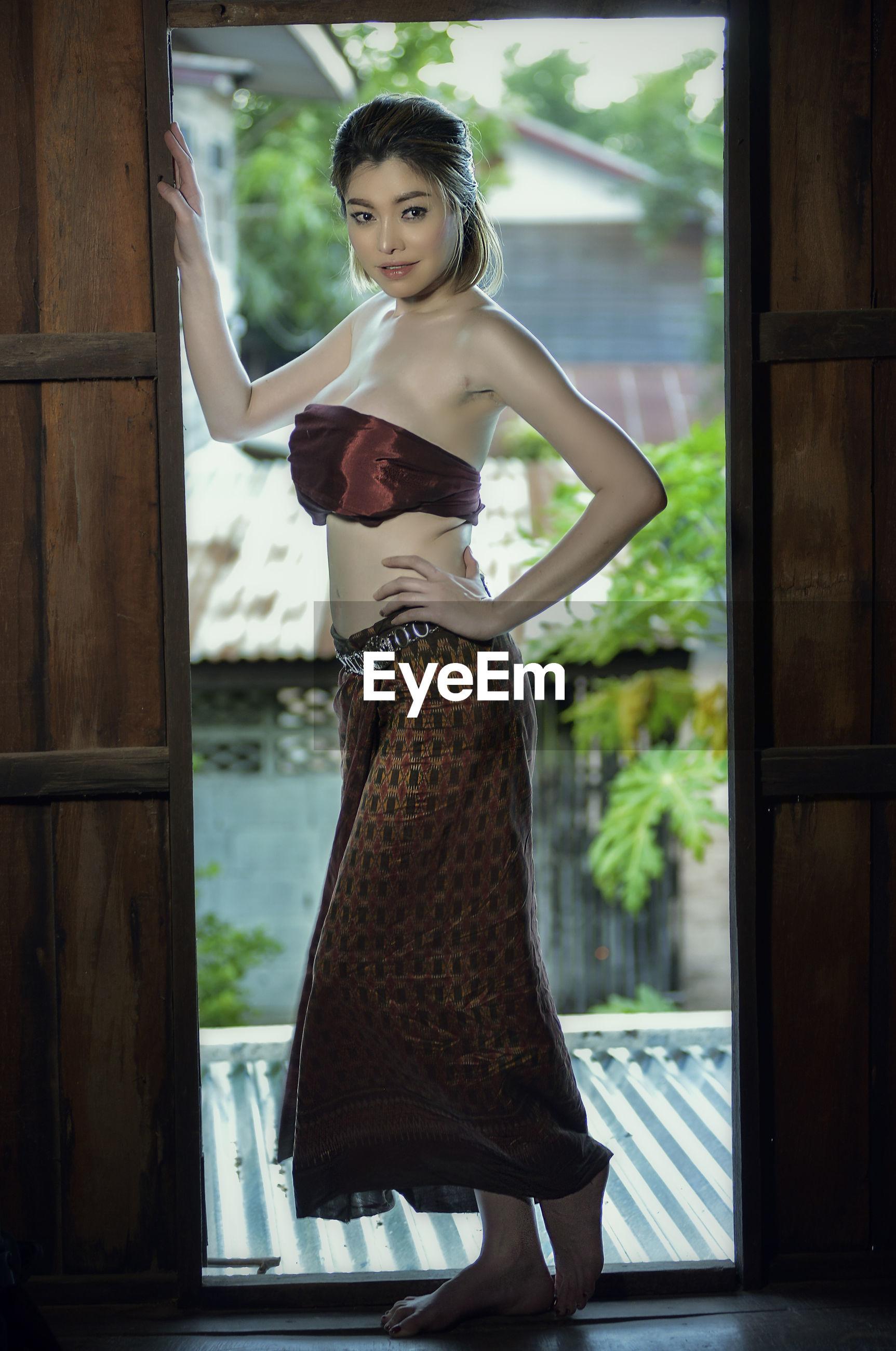 Portrait of young woman standing at doorway