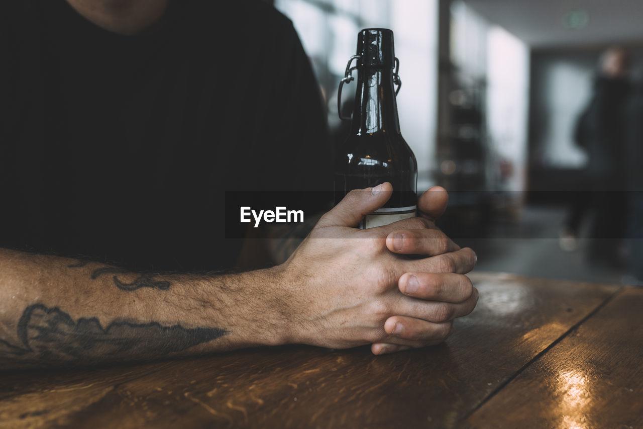 Close-up of man holding beer bottle