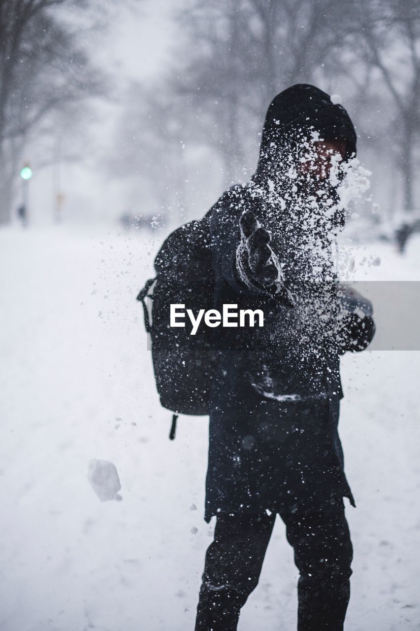 Person playing with snow while standing on field during winter