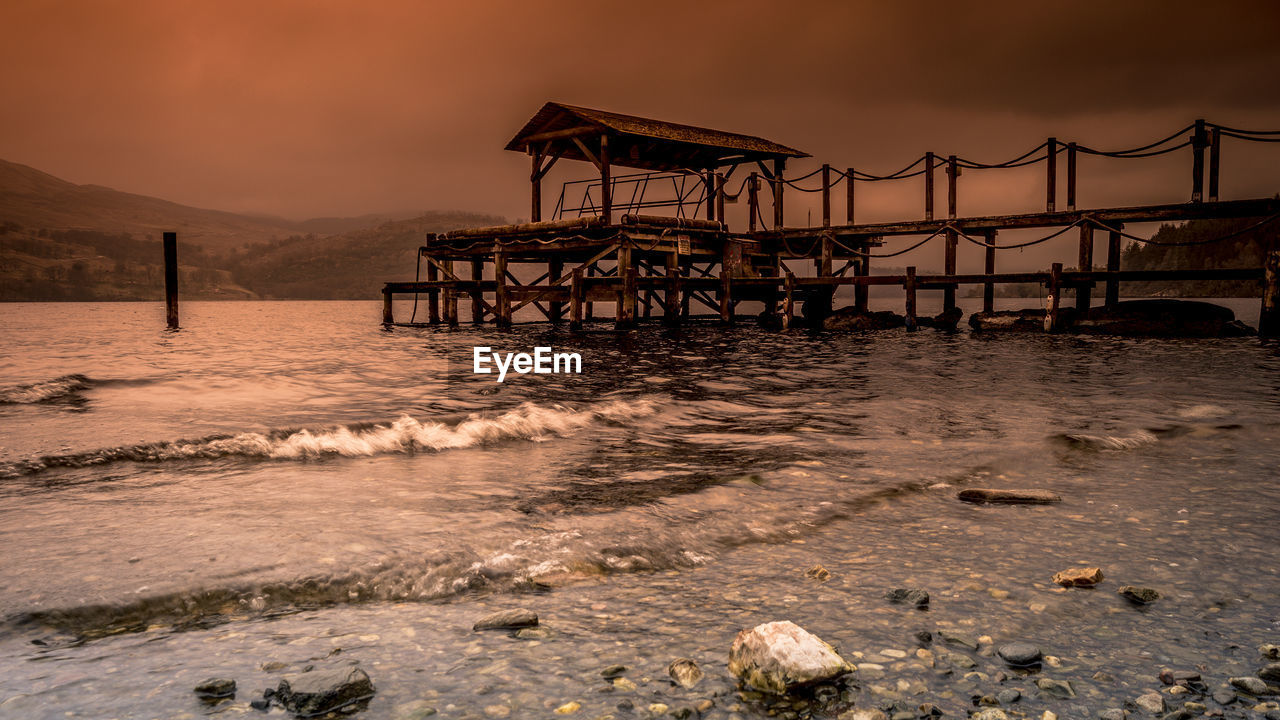 water, sky, sunset, architecture, built structure, sea, nature, beauty in nature, land, beach, no people, scenics - nature, pier, cloud - sky, tranquil scene, outdoors, motion, tranquility, mountain