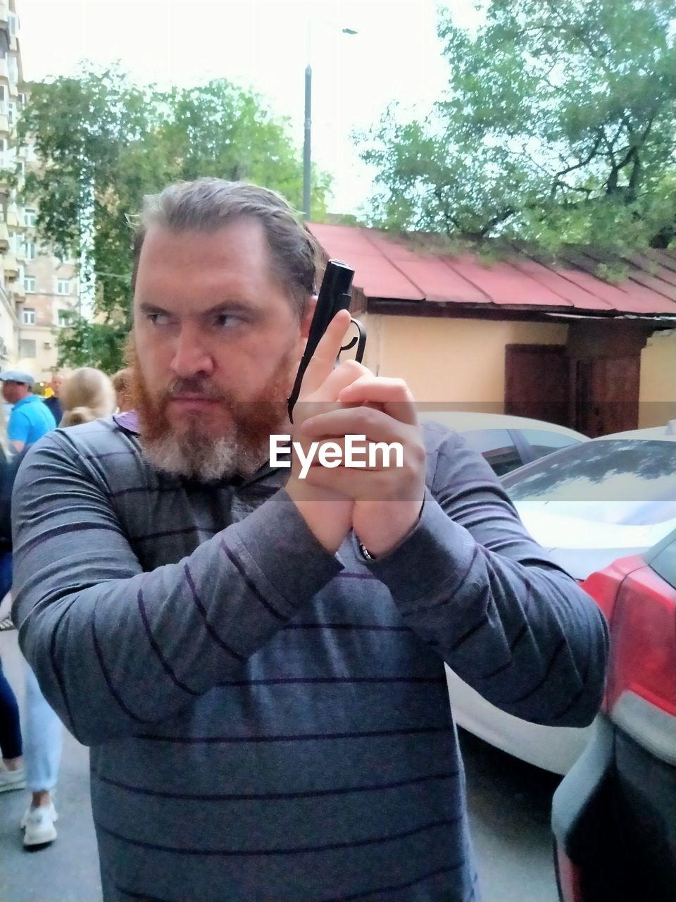PORTRAIT OF MAN USING SMART PHONE IN WINTER
