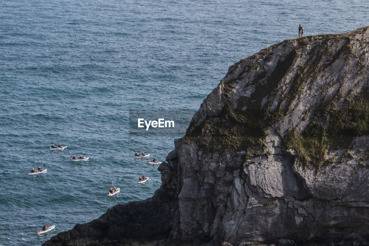 People On Cliff Looking At Boat Race In Sea