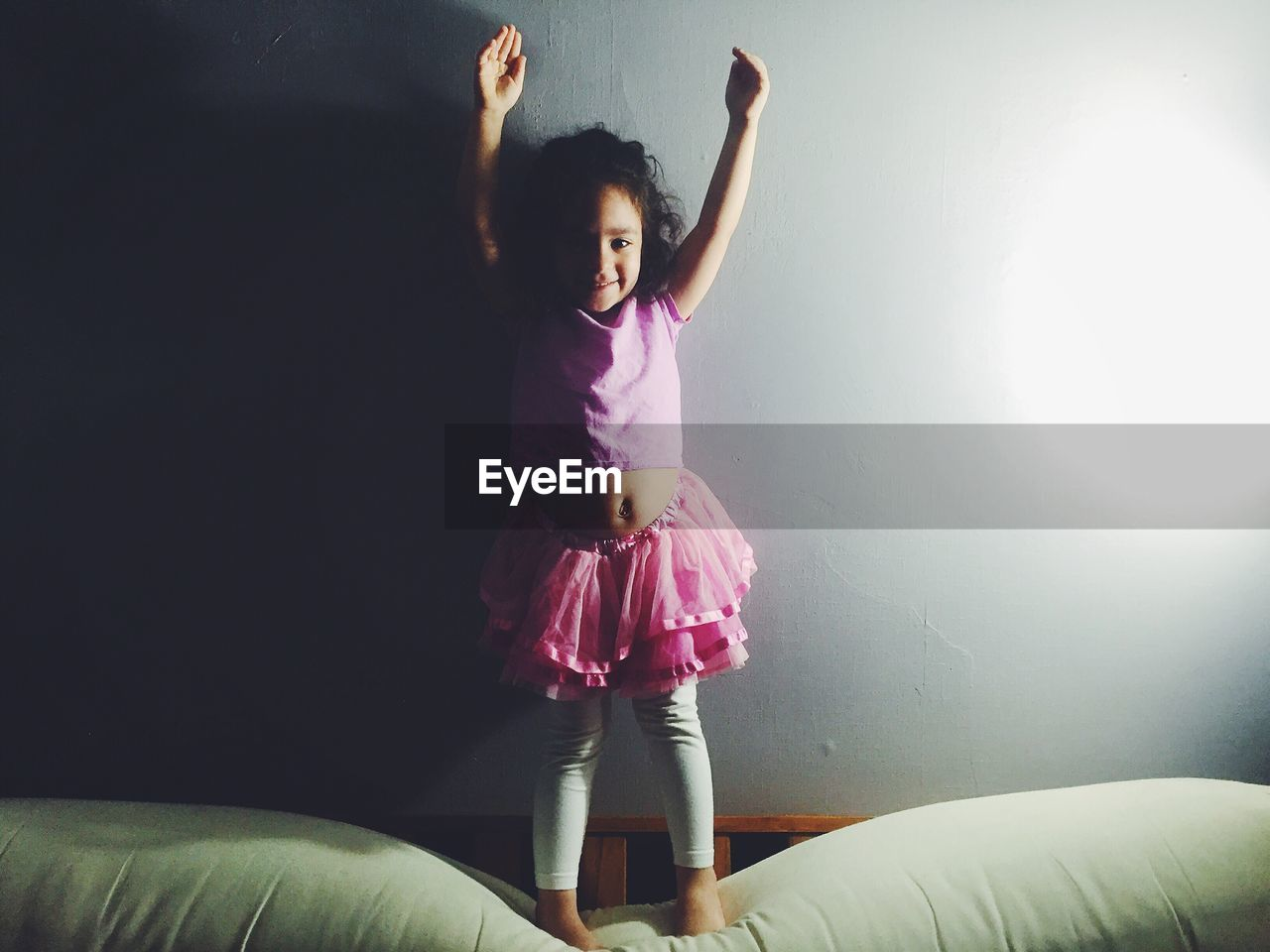 Portrait Of Happy Ballerina Standing On Bed With Arms Raised