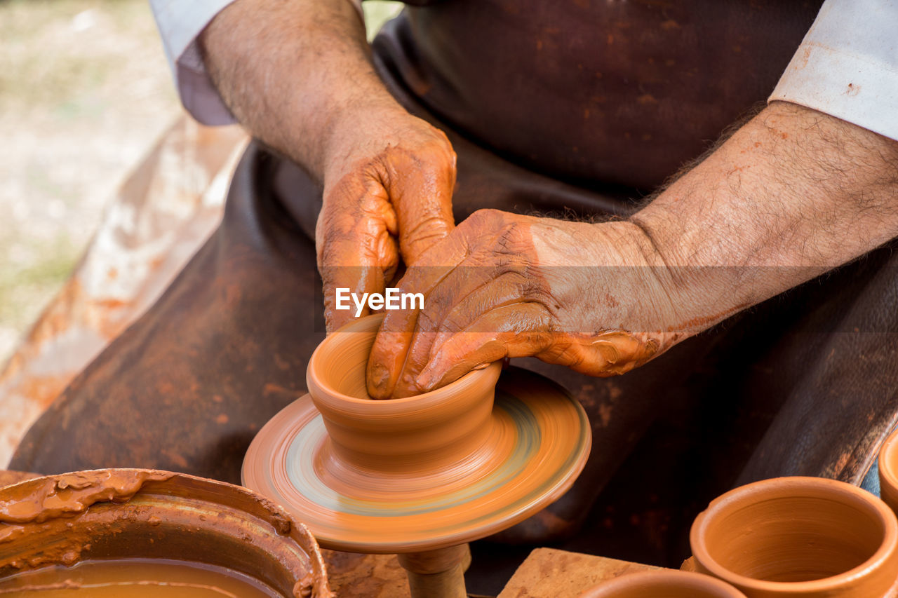 craft, occupation, art and craft, human hand, one person, skill, working, pottery, hand, making, real people, human body part, clay, expertise, creativity, men, molding a shape, spinning, ceramics, workshop, mud, preparation, outdoors