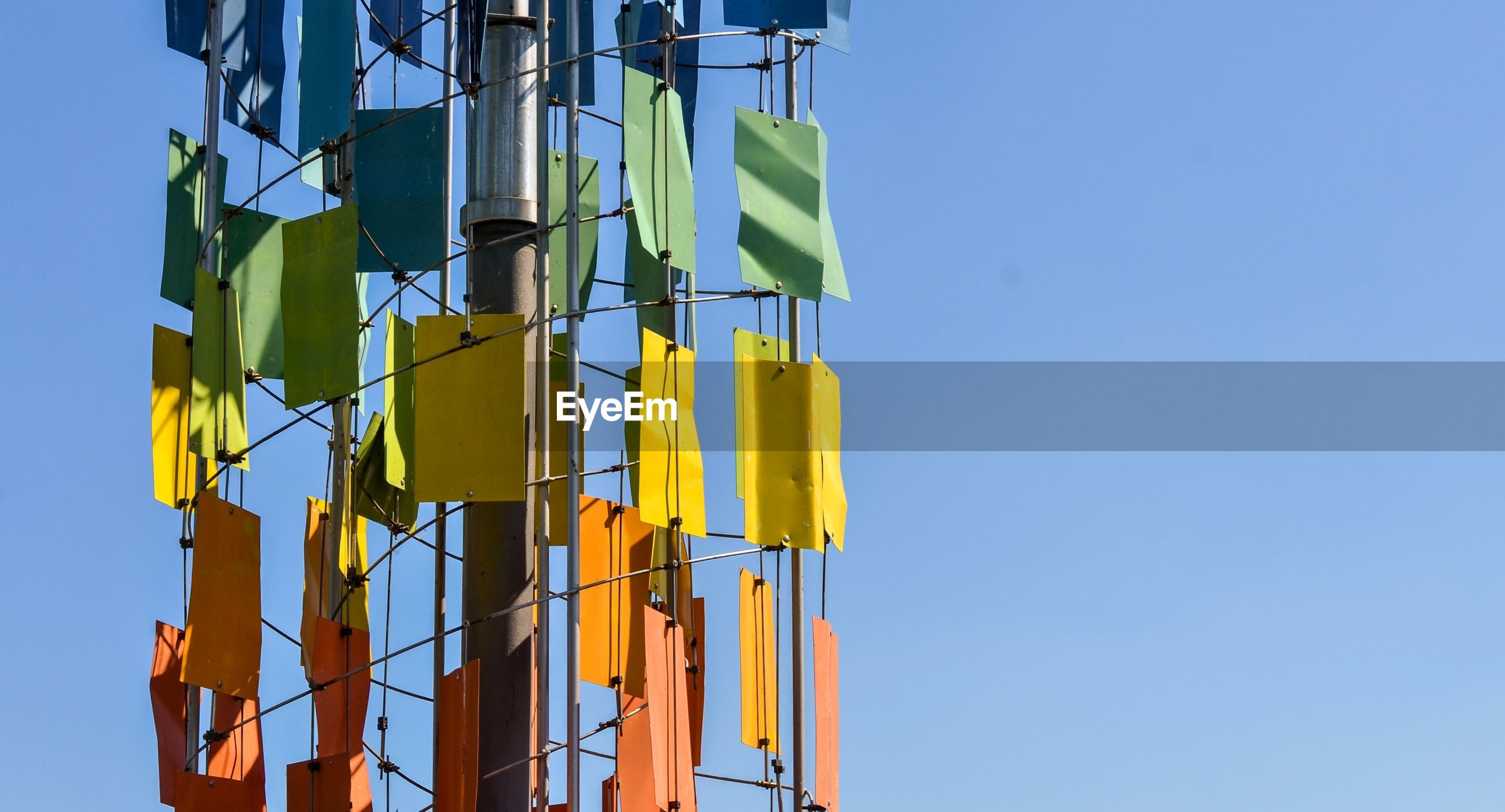 Close-up of multi colored communication tower against blue sky