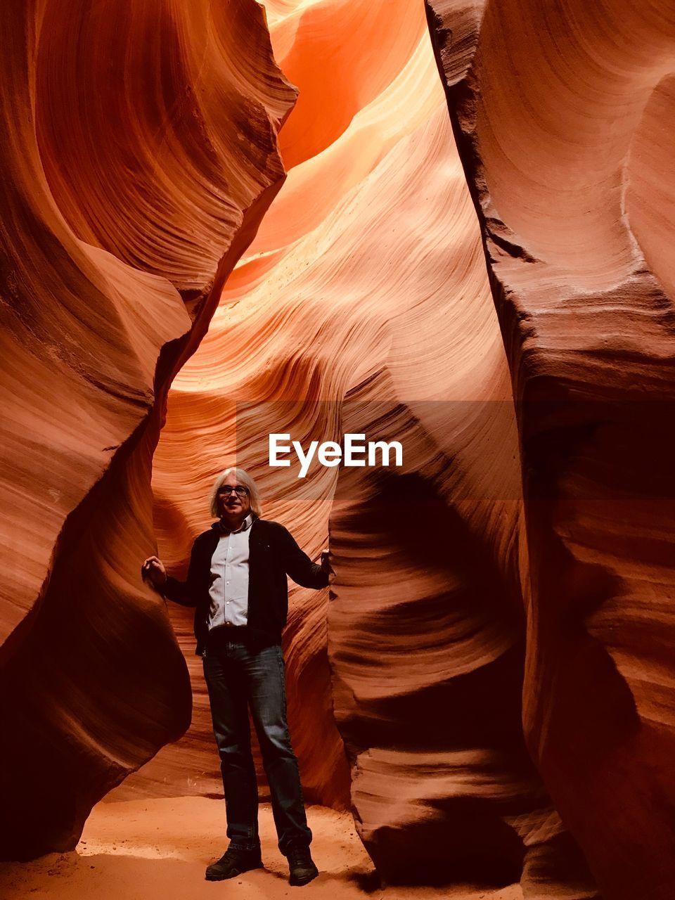 Portrait Of Man Standing By Rocks