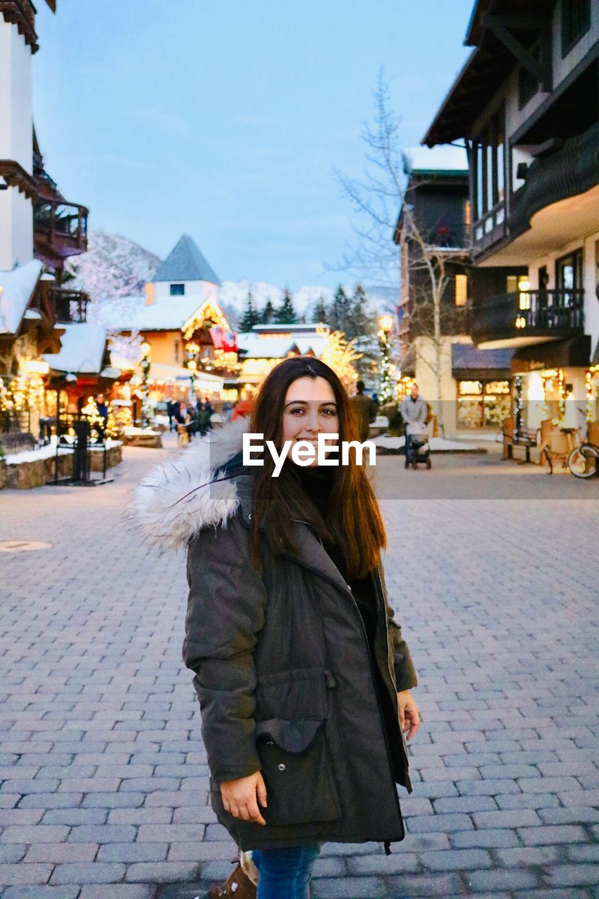 Portrait of smiling woman standing on street in city during winter
