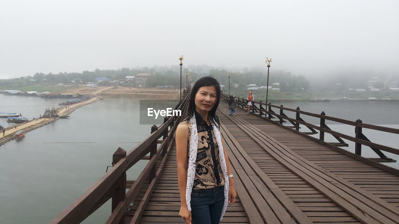 Portrait of woman standing on bridge over river