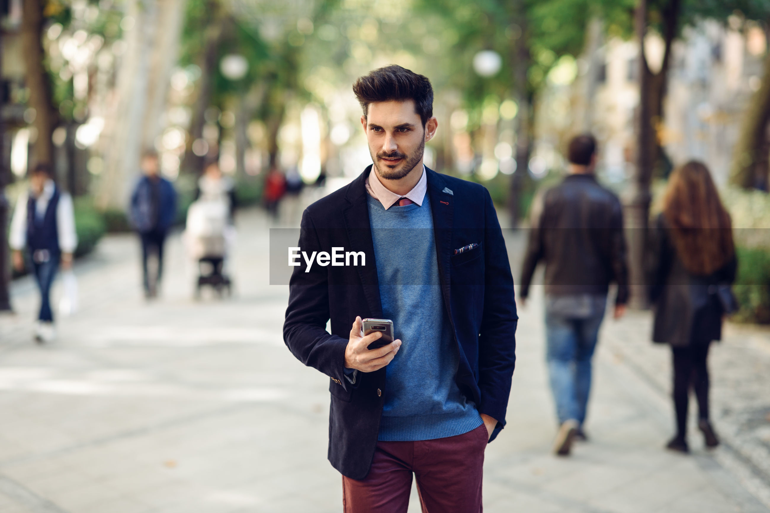 Young man using mobile phone while standing on footpath