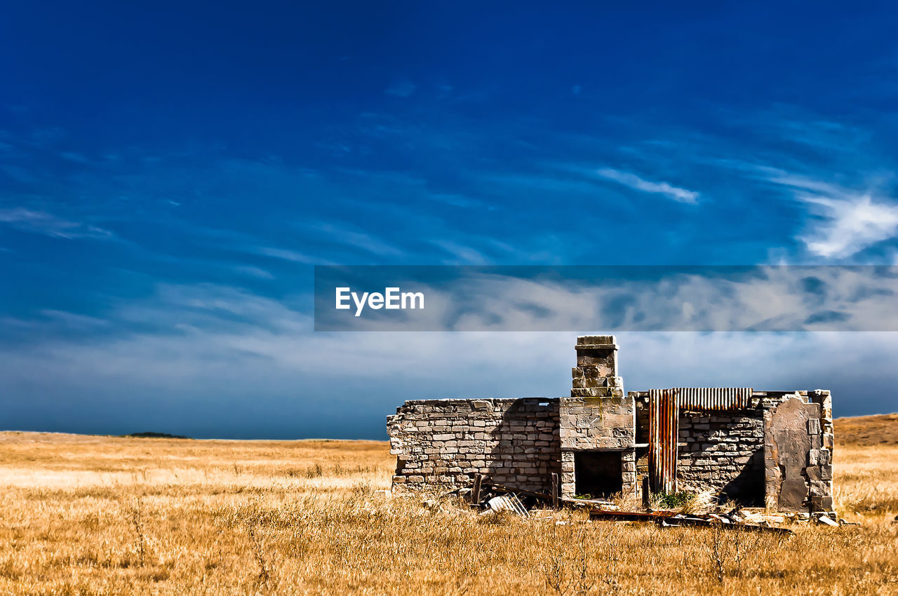 sky, cloud - sky, field, blue, architecture, land, abandoned, built structure, nature, damaged, history, run-down, old, building exterior, no people, the past, day, plant, obsolete, old ruin, deterioration, ruined, outdoors